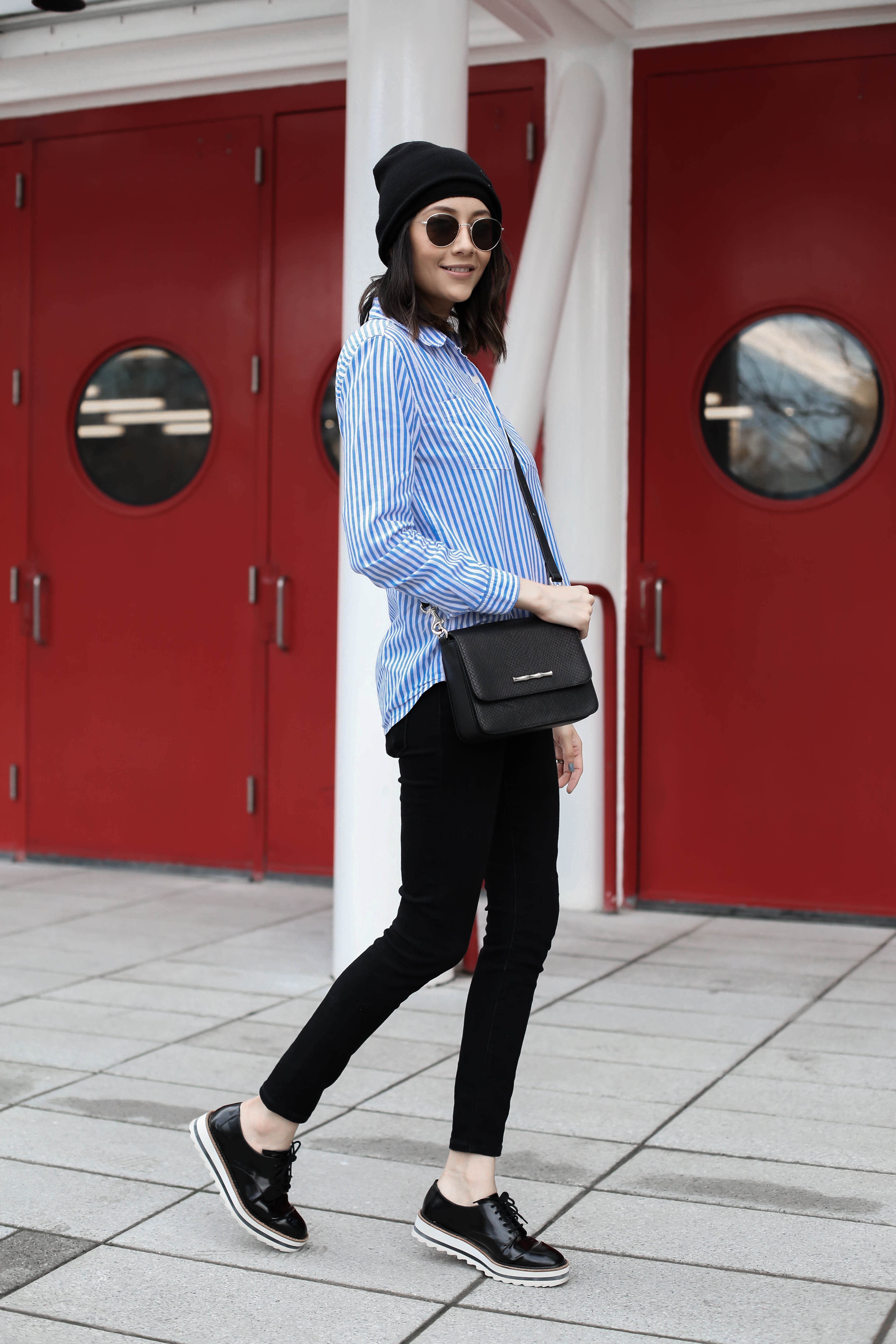 Lilly Beltran of Daily Craving in a fall outfit wearing black skinny jeans and striped button up shirt