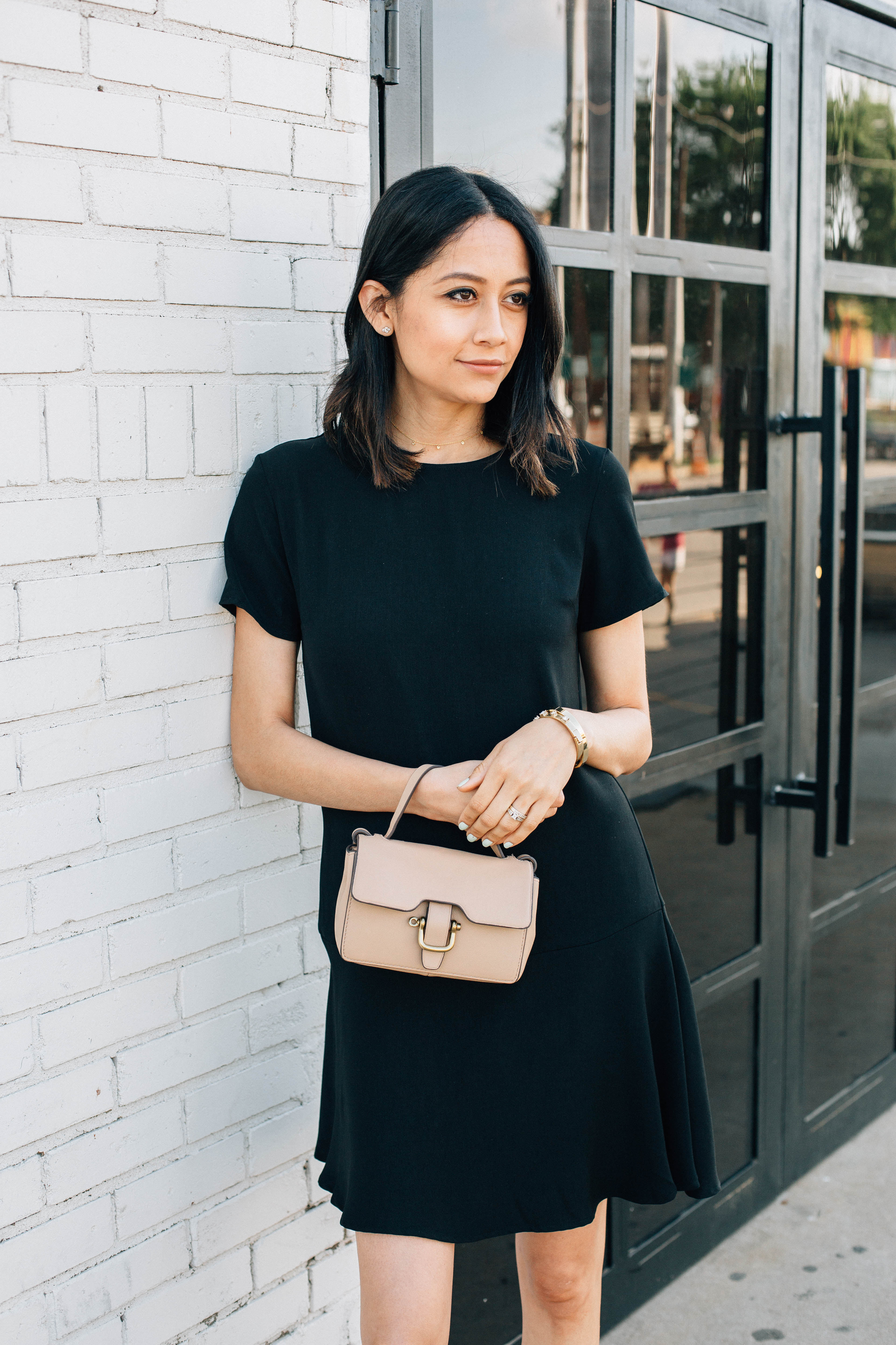Lilly Beltran of Daily Craving style blog wearing a LBD with a beige mini cross body bag