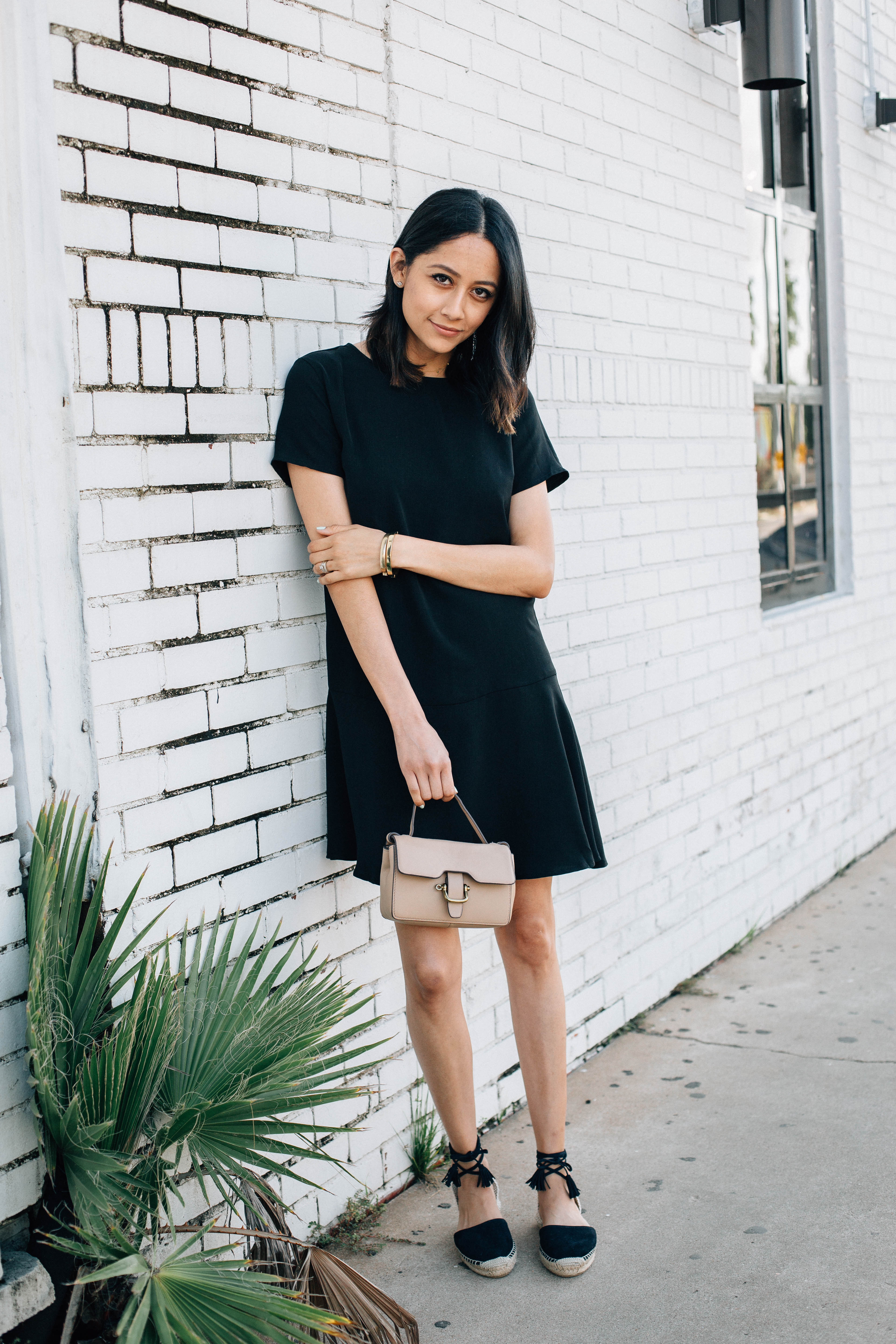 Style blogger Lilly Beltran of Daily Craving in a casual look wearing a black dress and black tassel espadrilles