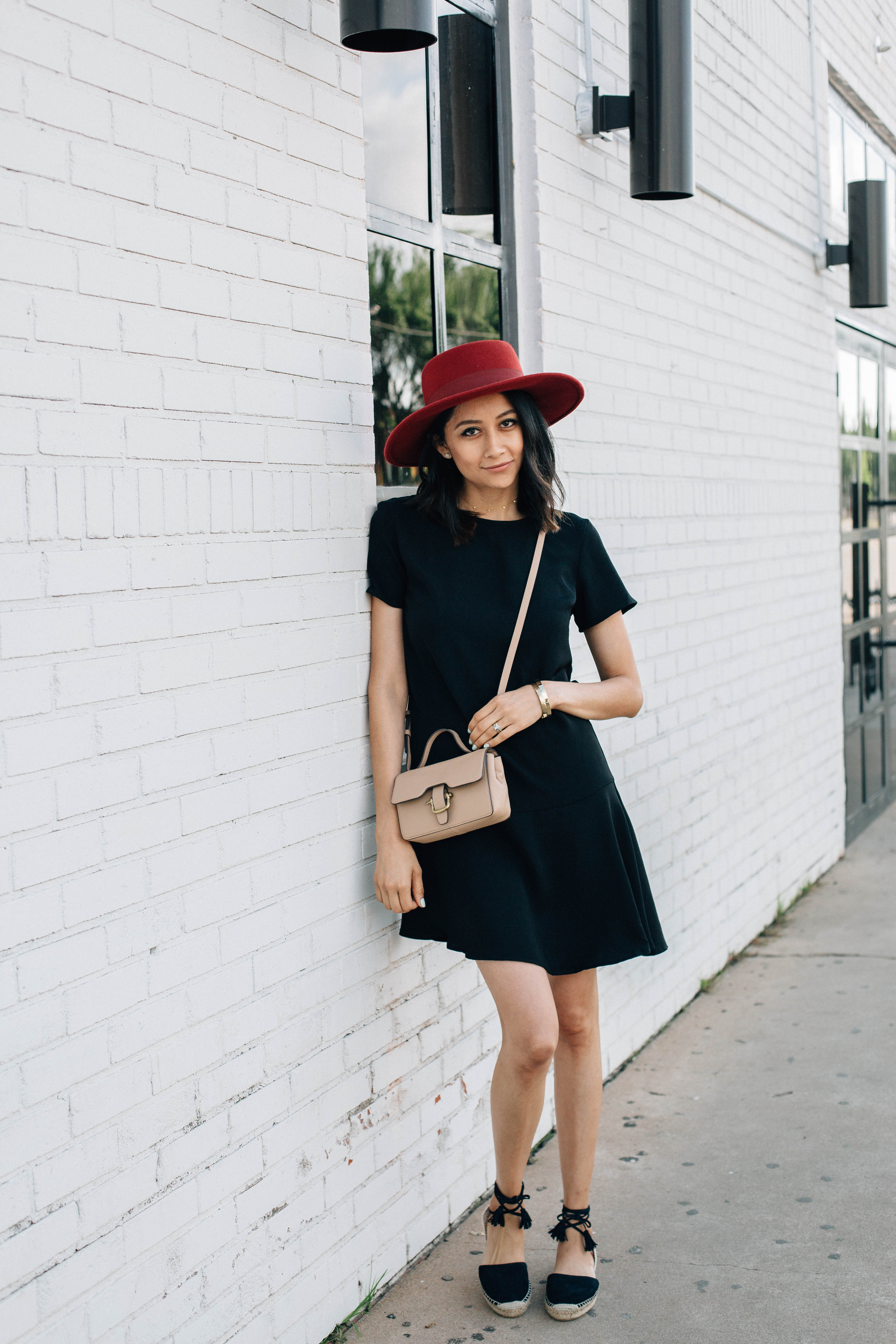 Lilly Beltran of Daily Craving blog styles a LBD with a red hat, black espadrilles and a J.Crew beige cross body bag