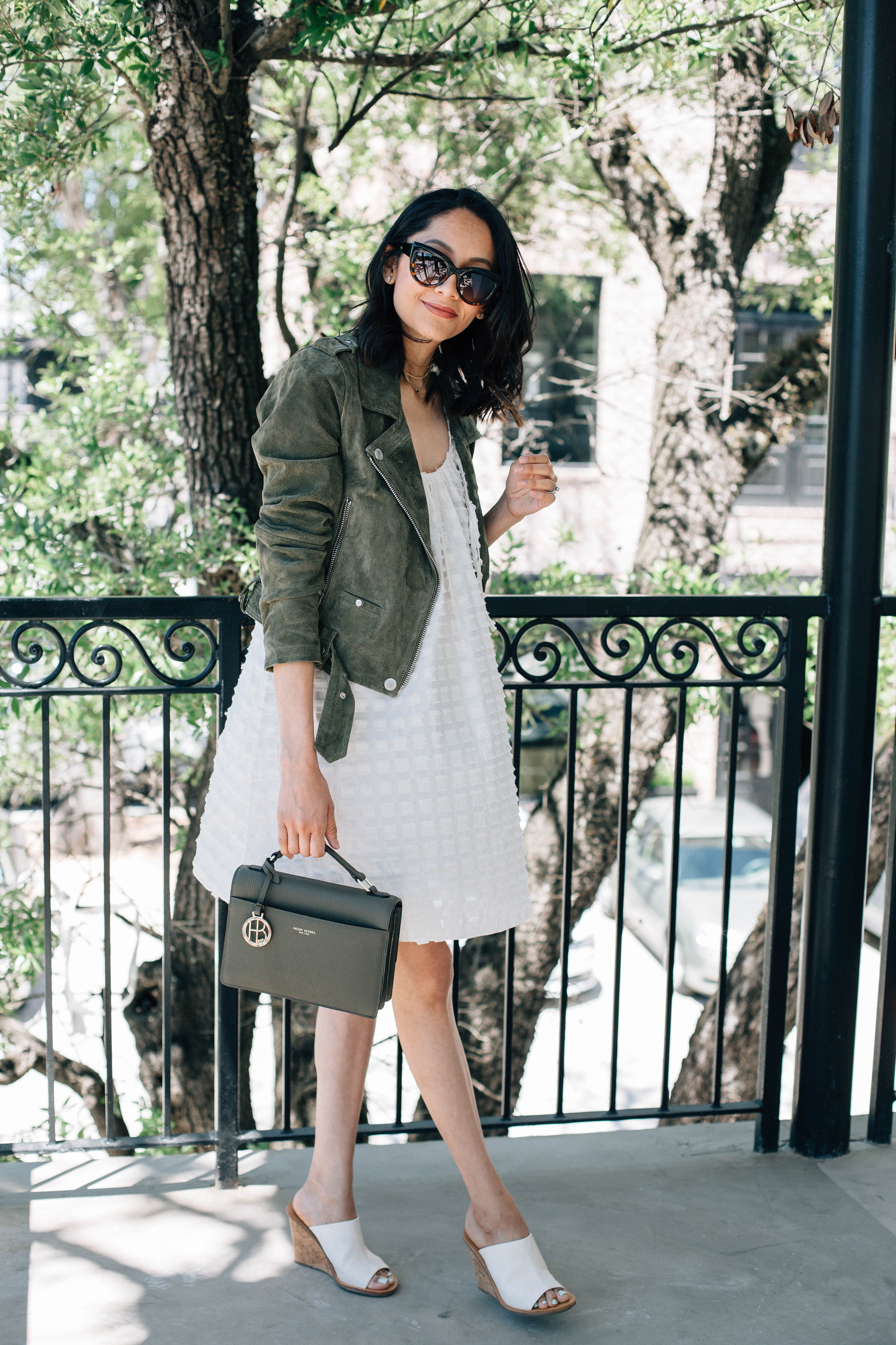 Lilly Beltran of Daily Craving blog wearing a sundress with a green suede moto jacket
