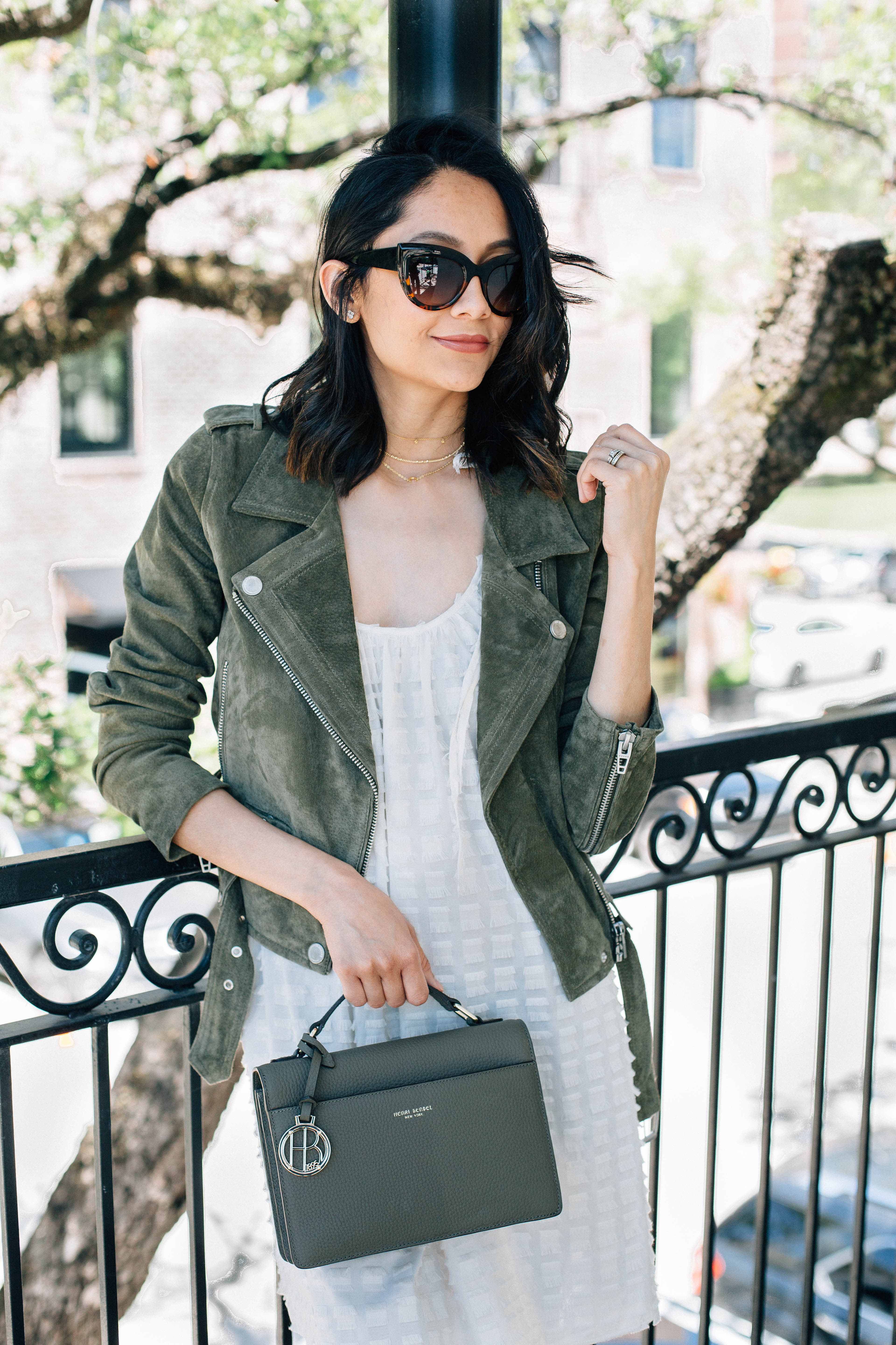 Lifestyle blogger Lilly Beltran of Daily Craving wearing a suede motto jacket and Henri Bendel Bag