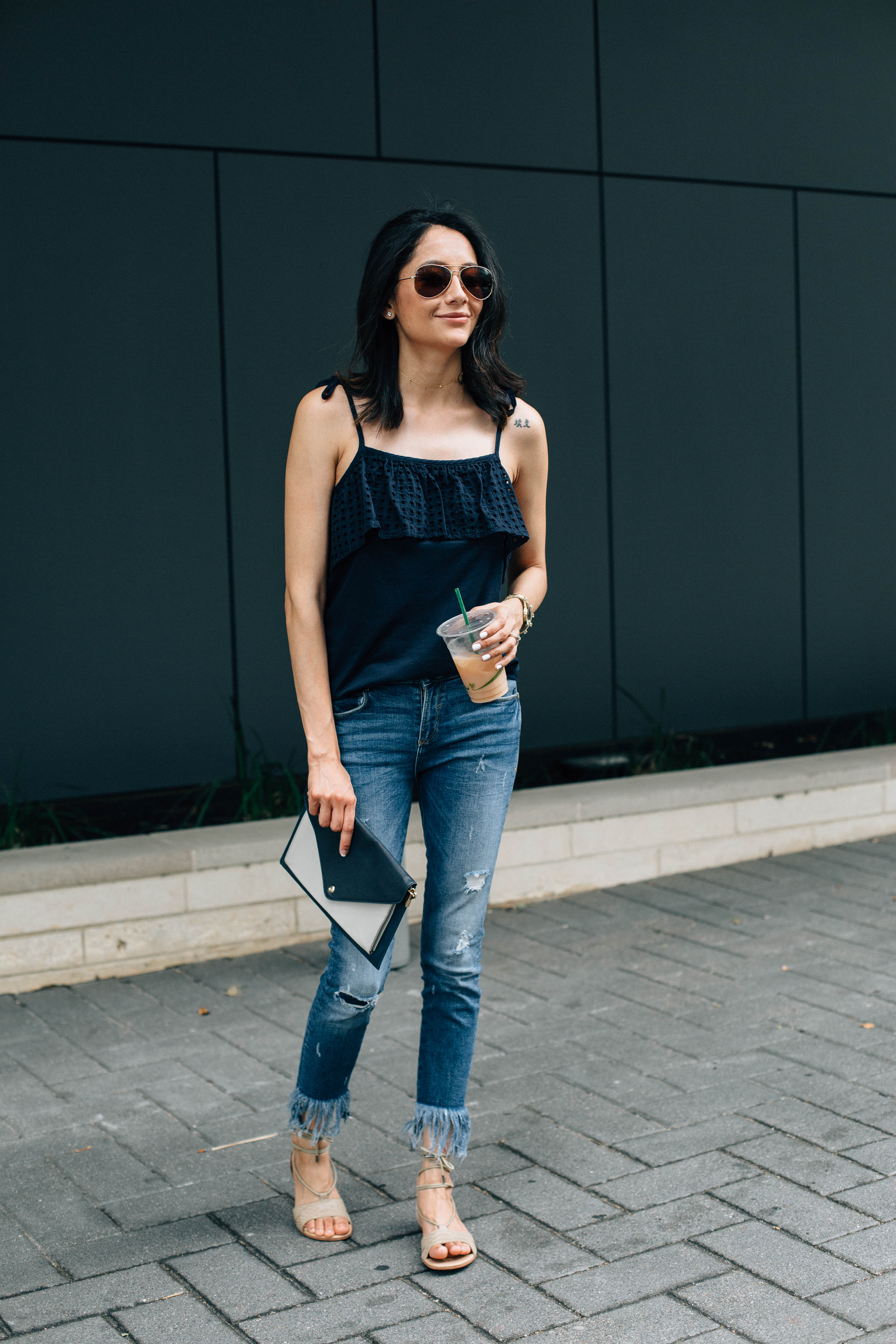 Lilly Beltran of Daily Craving wearing a navy eyelet top and denim jeans