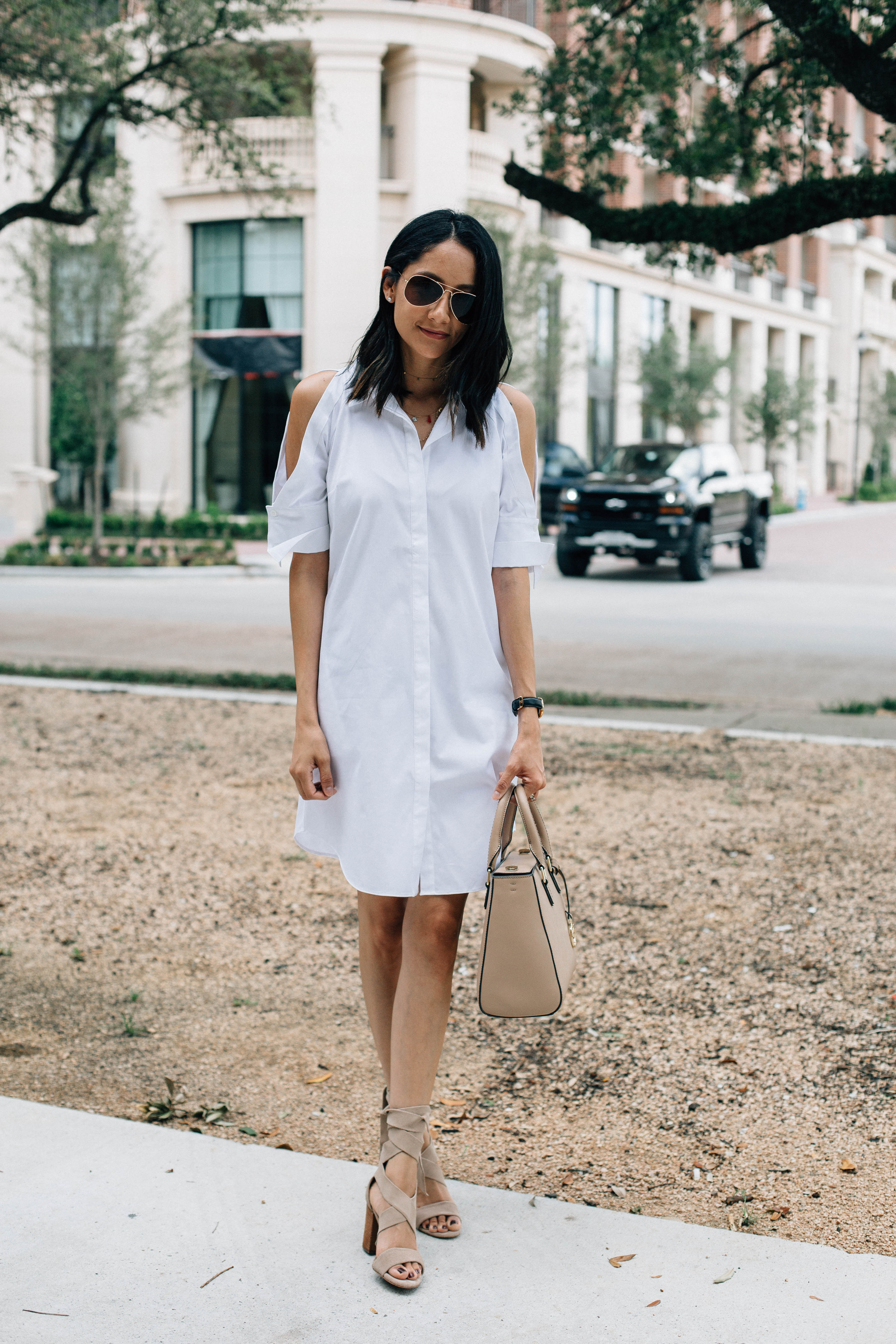 Lifestyle blogger of Daily Craving wearing a white Rachel Roy dress, Henri Bendel Bag and suede lace up sandals
