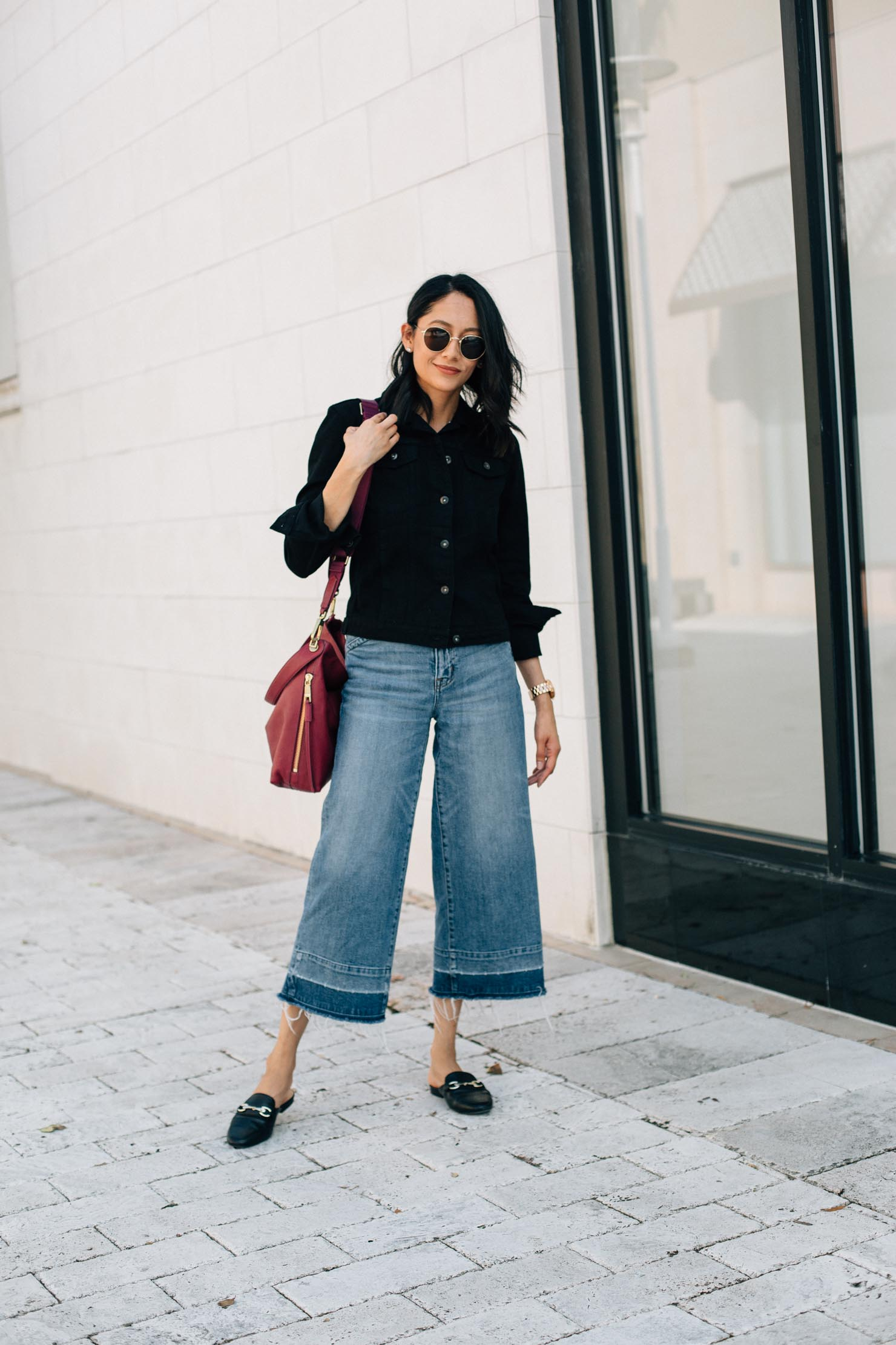 Lilly Beltran of Daily Craving blog shows her fall style in a black denim jacket and wide leg denim pants