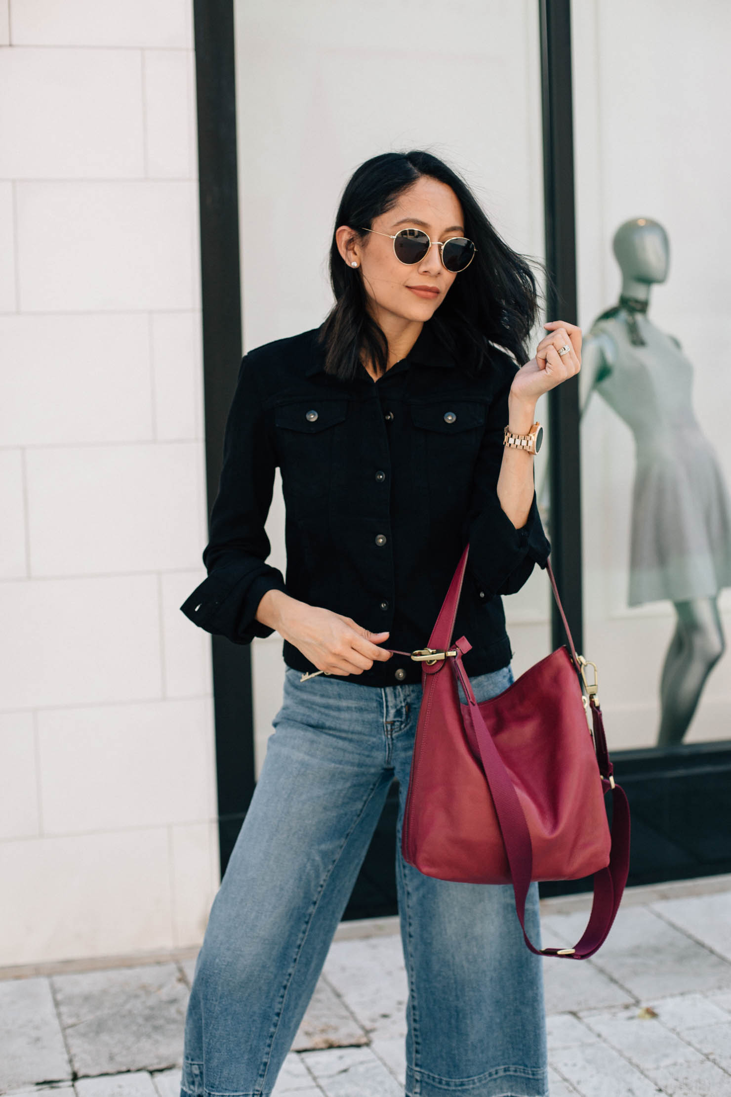 Lilly Beltran of Daily Craving blog wearing a black denim jacket and a Fossil boho bag