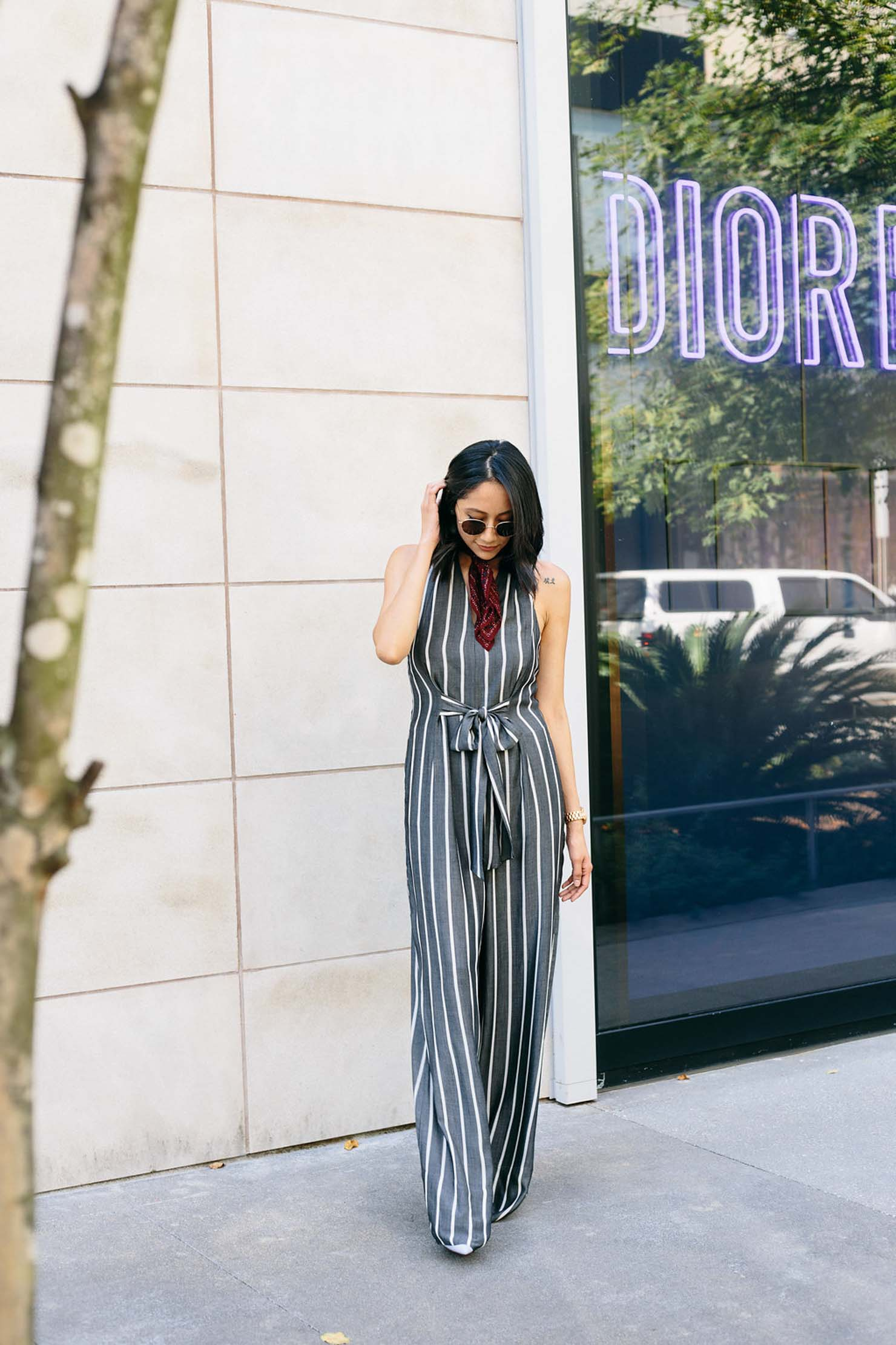 Lilly Beltran of Daily Craving blog in a casual cool look wearing a grey striped jumpsuit