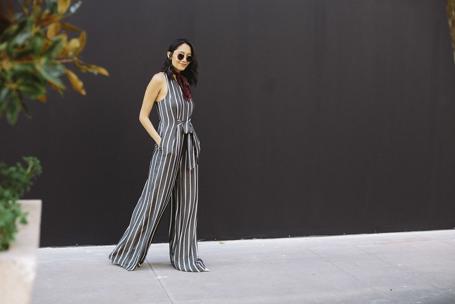 Fashion blogger Lilly Beltran of Daily Craving wearing a Rachel Roy striped jumpsuit with a red neckerchief and round sunglasses