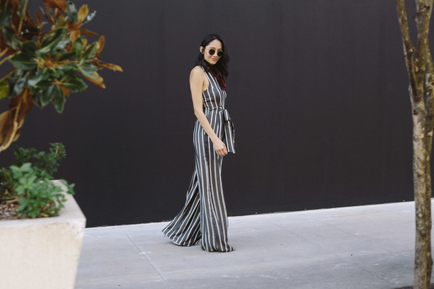 Style blogger Lilly Beltran of Daily Craving wearing a Rachel Roy striped jumpsuit with a Burgundy bandana and round sunglasses