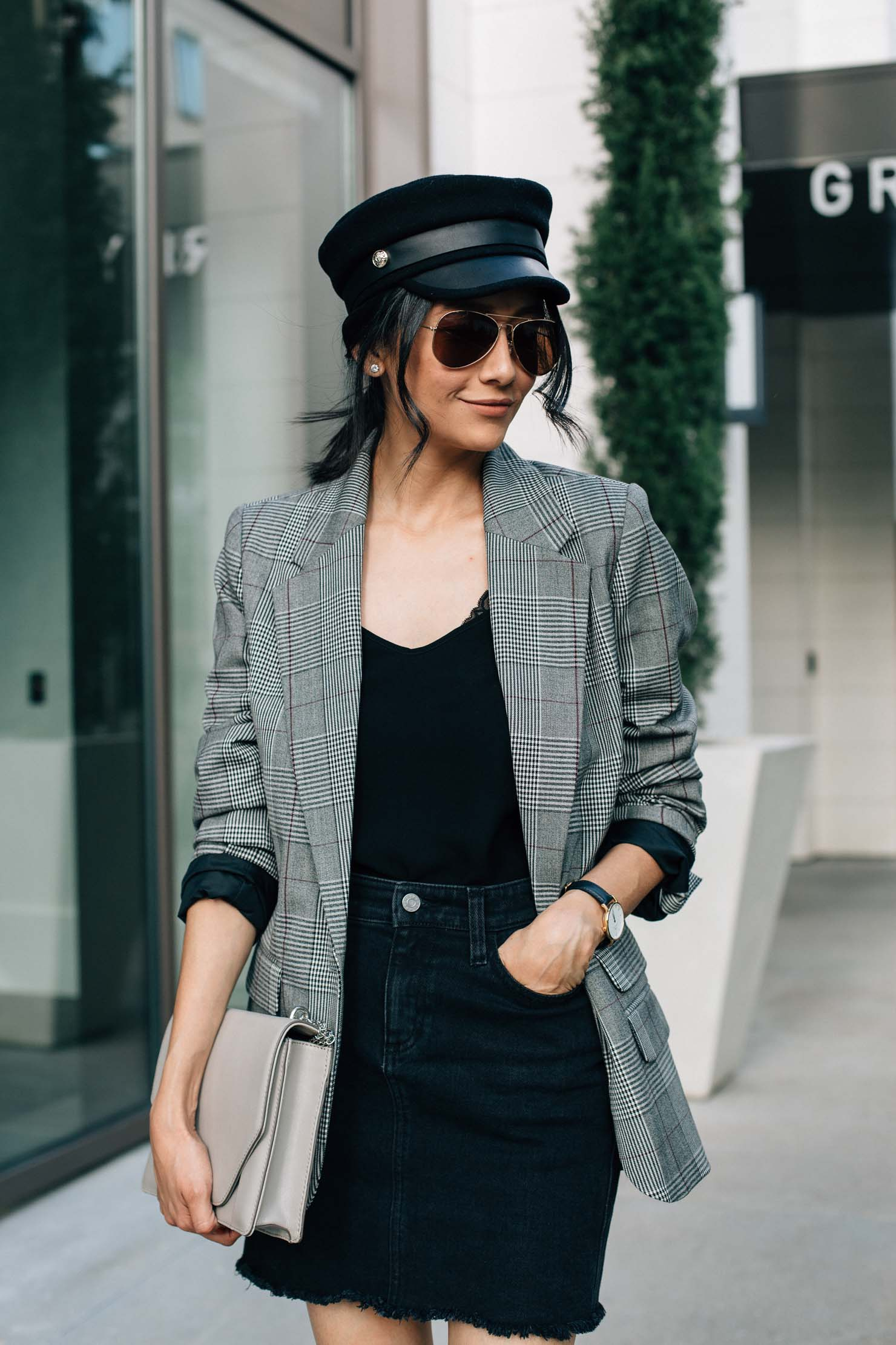 Style blogger Lilly Beltran in a trendy fall look with a black denim skirt, plaid blazer and baker boy hat