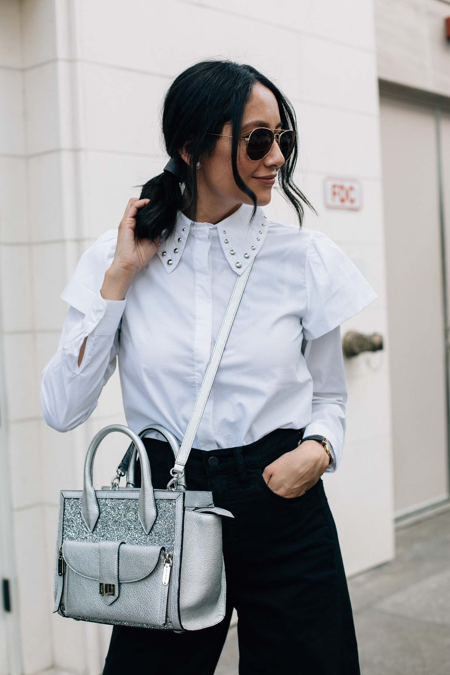 Style blogger Lilly Beltran of Daily Craving in a chic look wearing a white shirt with stud and ruffle detail, black denim culottes and metallic Henri Bendel bag