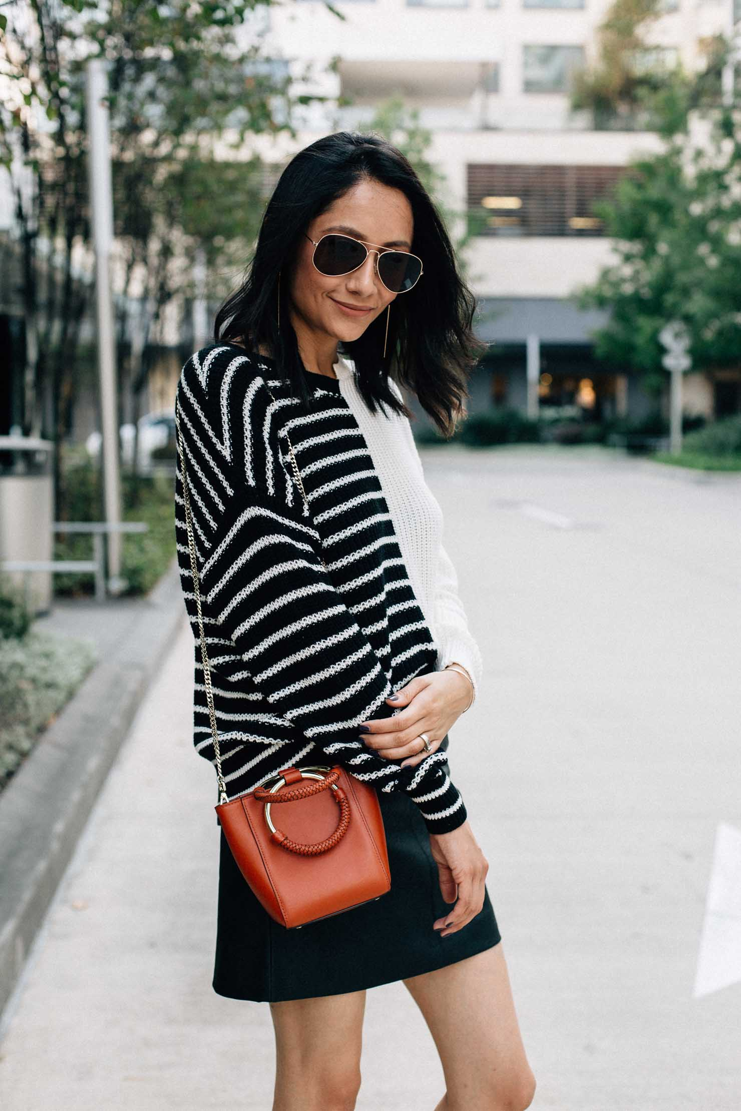 Style blogger Lilly Beltran in a fall outfit with a faux leather mini skirt and oversized striped sweater