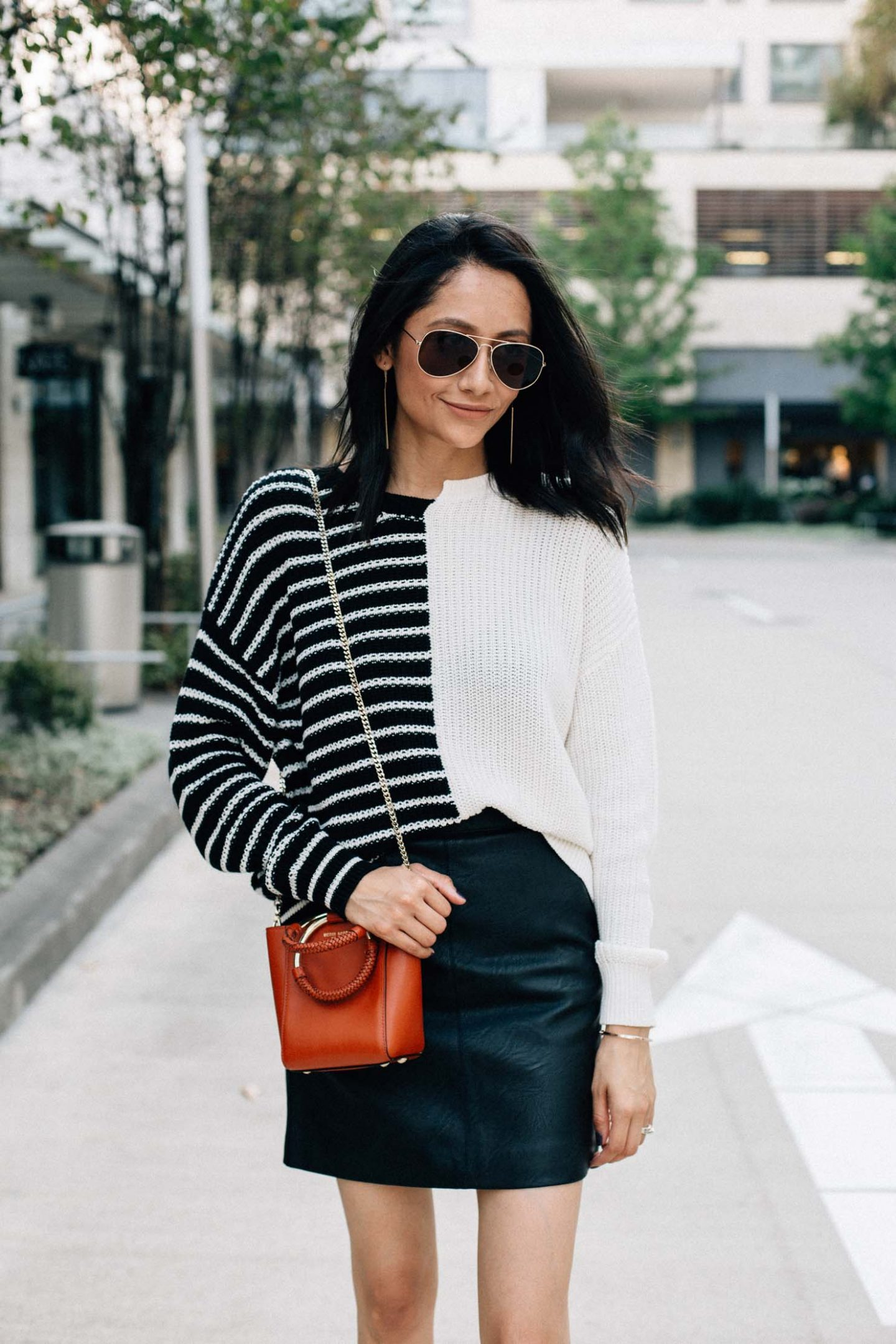 Style blogger Daily Craving wearing a fall look with a leather mini skirt, striped sweater and black patent leather boots