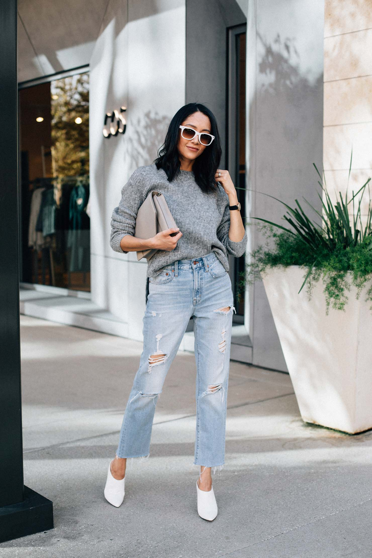 Fashion blogger Lilly Beltran in a casual fall outfit with a grey sweater, vintage denim & white mules