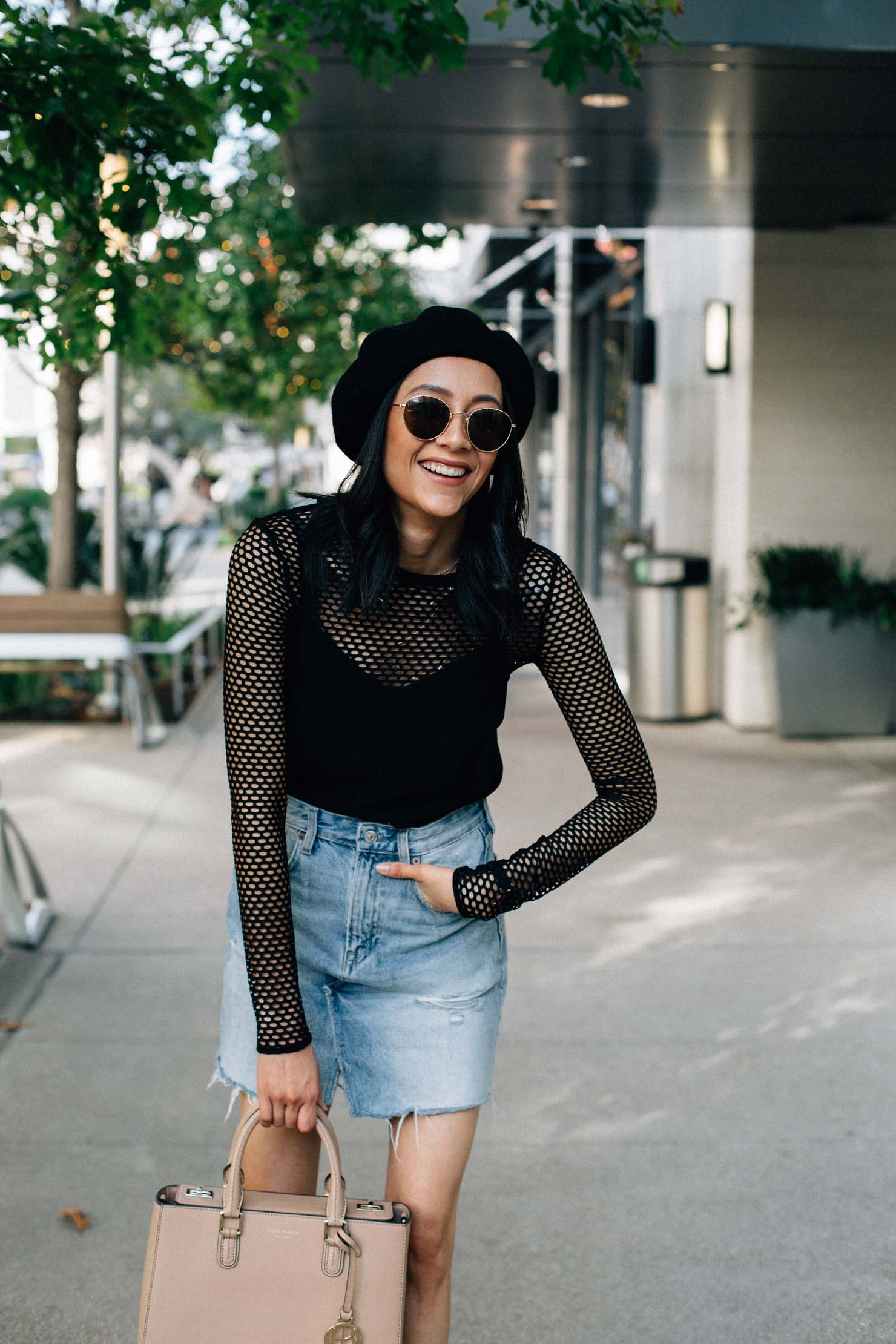 Fashion blogger Lilly Beltran wearing a long sleeve mesh top with a denim mini skirt and black beret