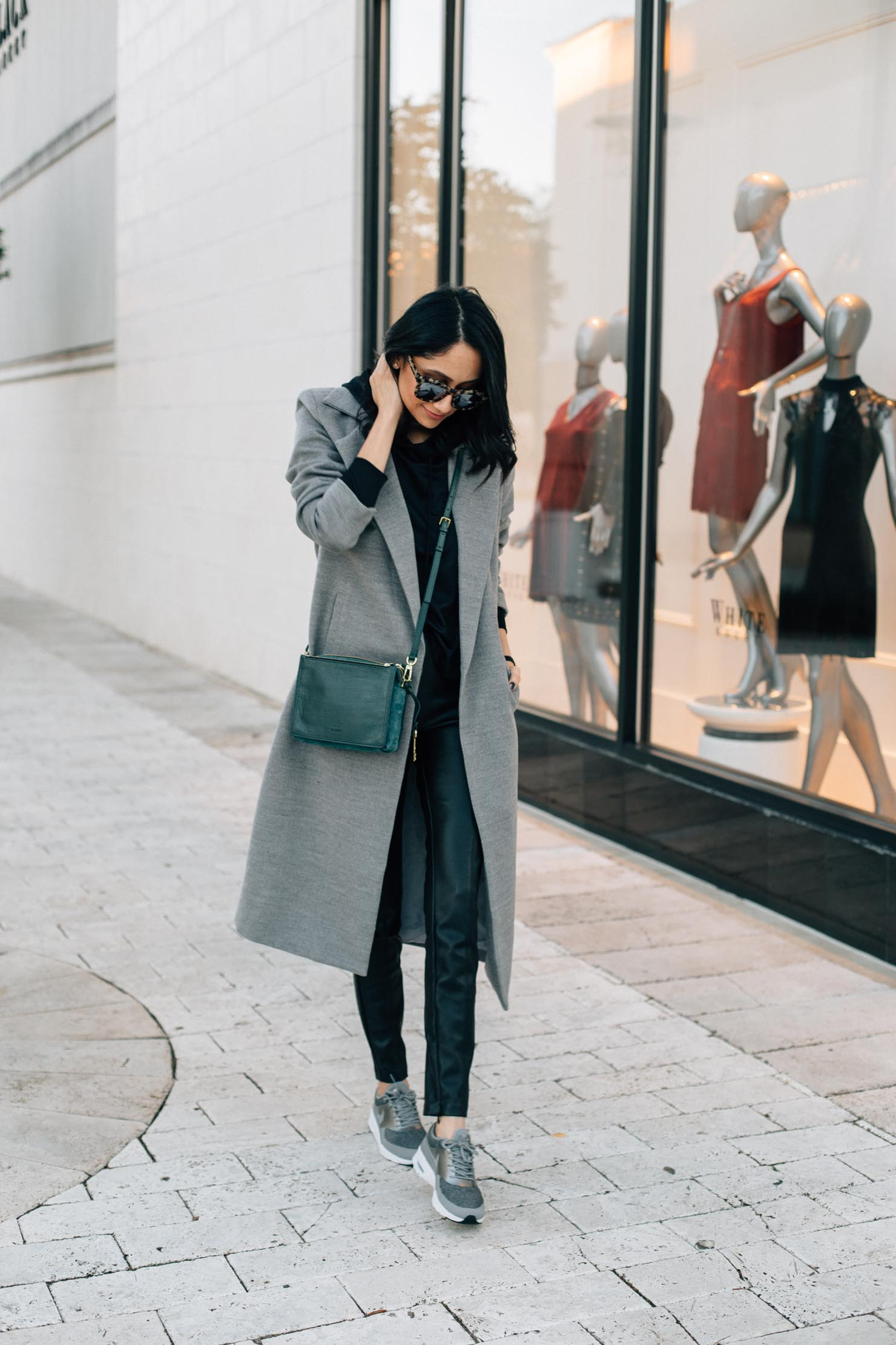 Lilly Beltran of Daily Craving styles a pair of black leather leggings with grey Nike sneakers and grey coat for a street chic look