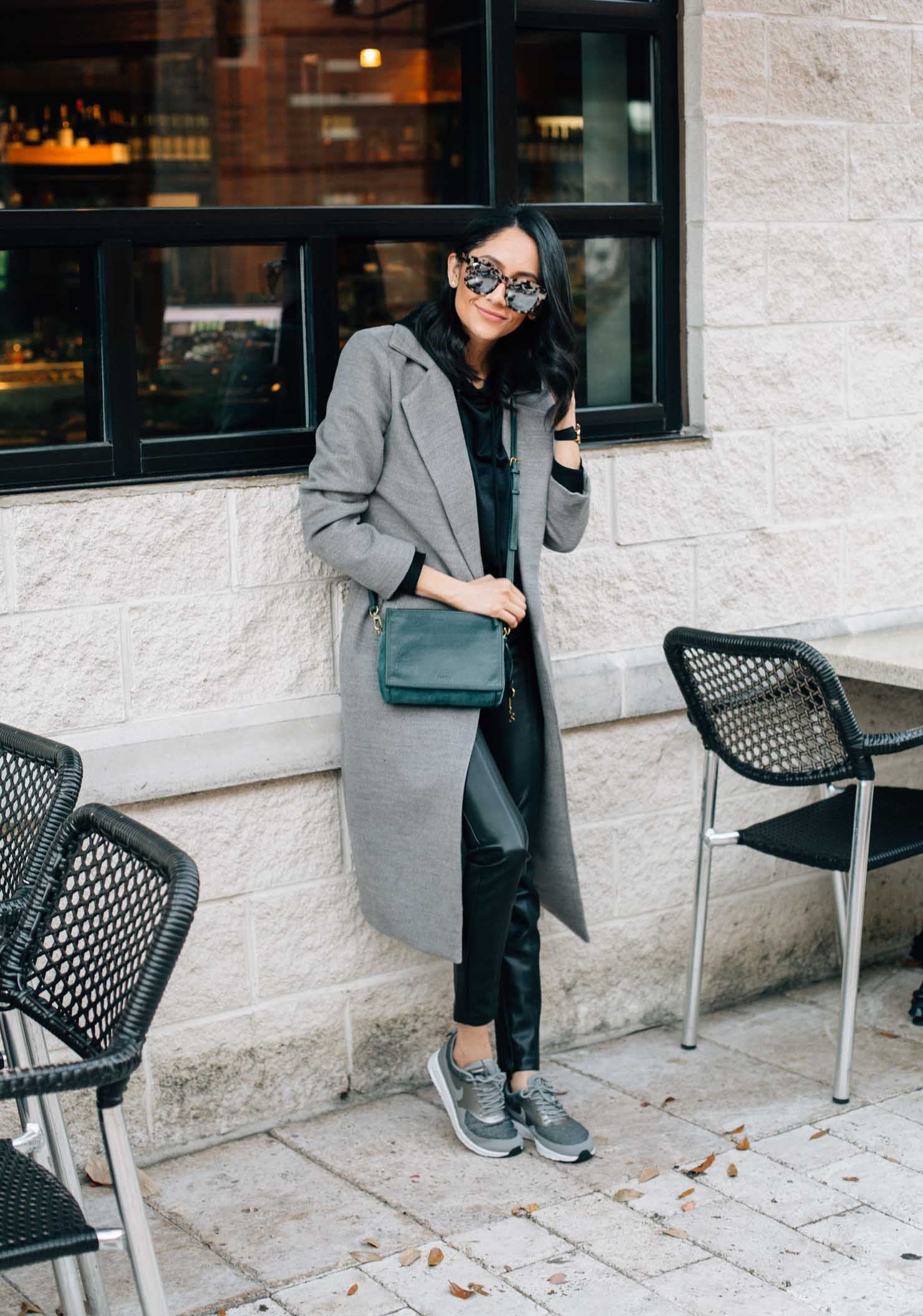 Lilly Beltran of Daily Craving blog styles black leather Moto leggings with Frey nike Thea sneakers and a grey maxi wool coat for a casual fall look