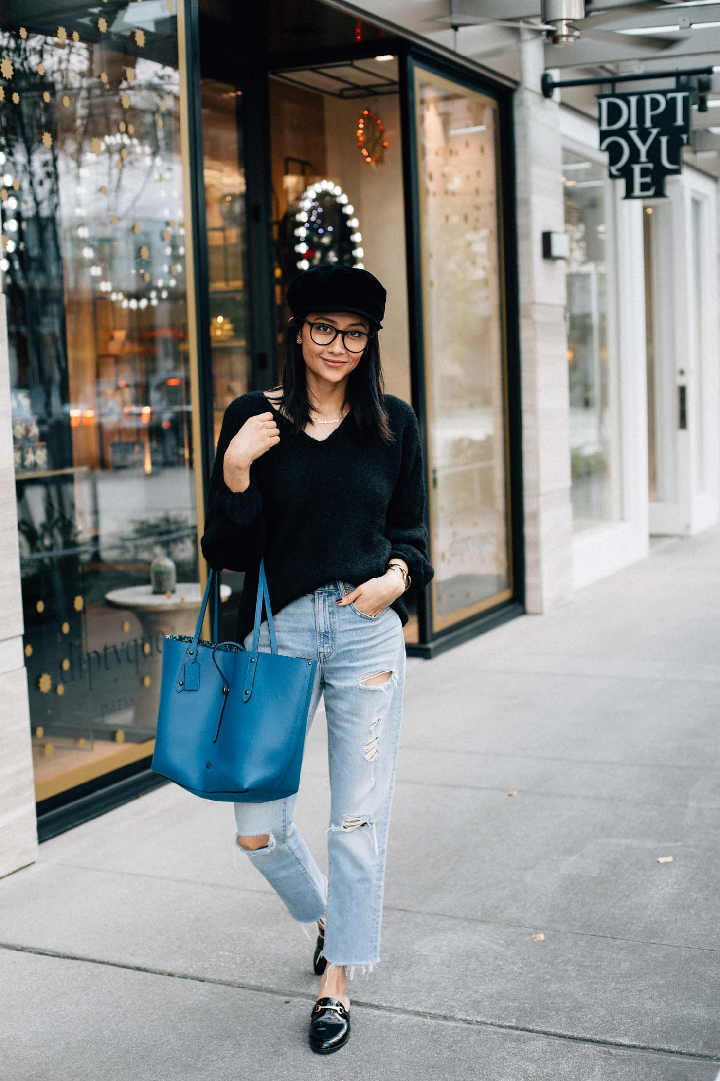 Lilly Beltran in a casual fall outfit with ripped denim black oversized sweater, bakerboy hat & blue bag