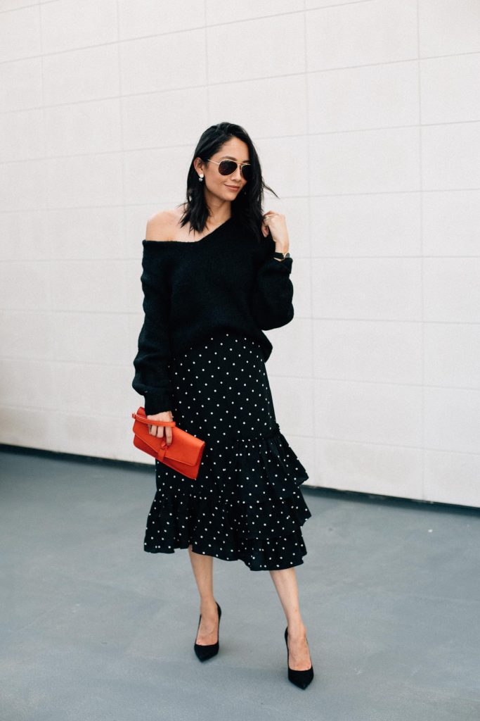 Lilly Beltran in a fall outfit with a  polka dot midi skirt and oversized sweater.