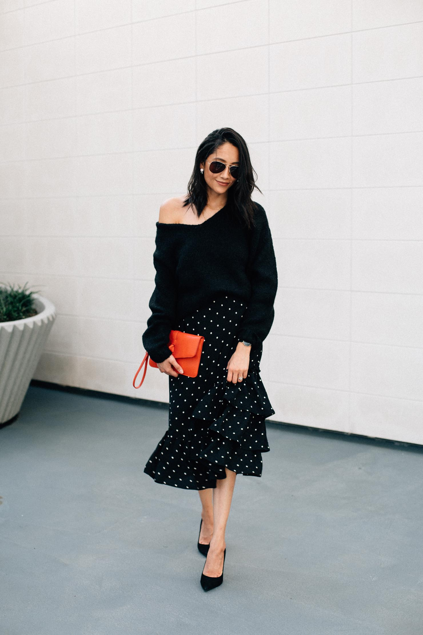 Fashion blogger Lilly Beltran of Daily Craving wearing a polka dot midi skirt with an oversized sweater for a Thanksgiving Day outfit idea