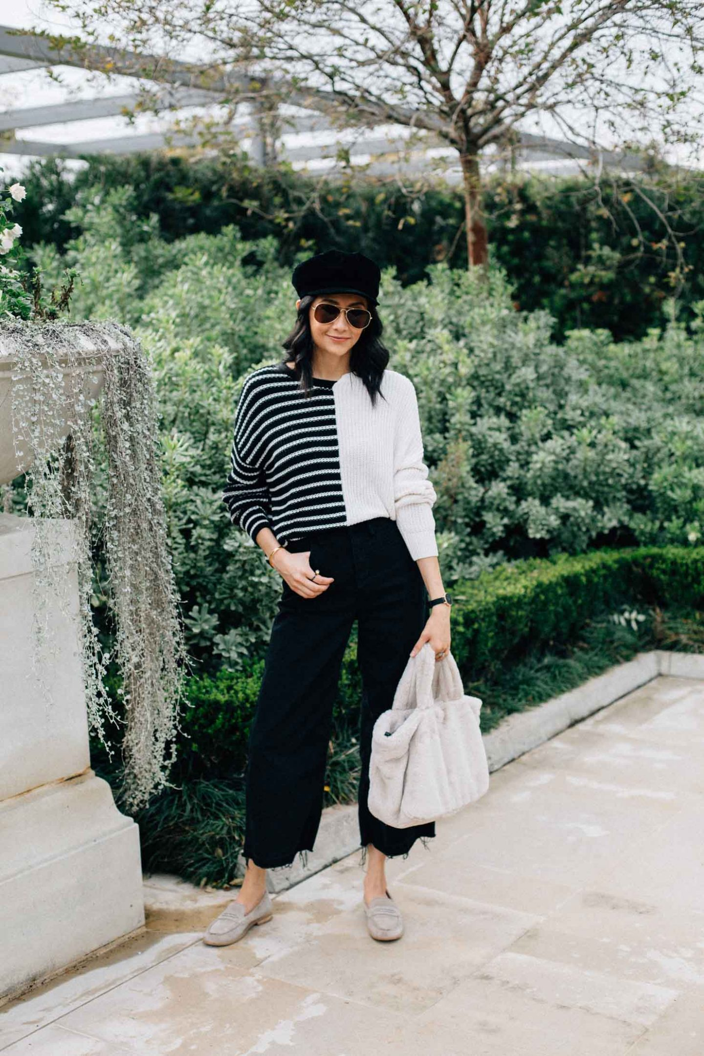Lilly Beltran of Daily Craving blog wearing an effortless look with black wide leg denim, a color block sweater, baker boy cap & faux fur bag