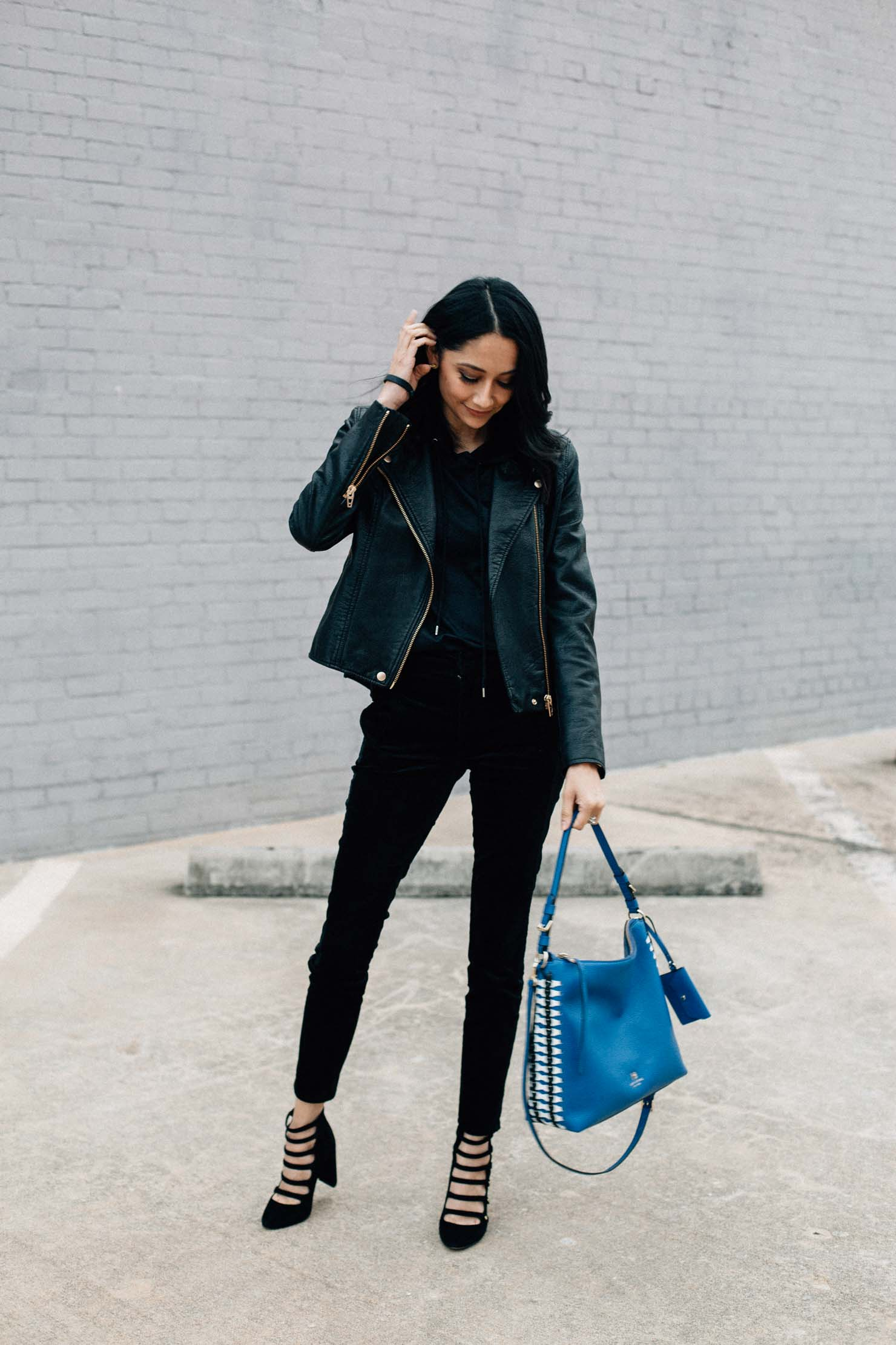 Lilly Beltran wearing a chic all black outfit with skinny velvet pants and faux leather moto jacket