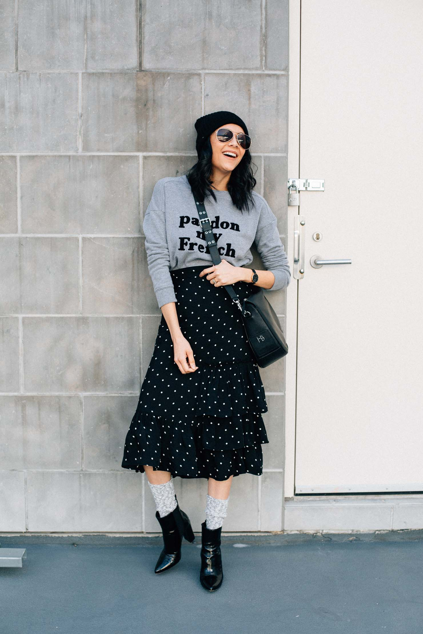 Lilly Beltran of Daily Craving wears boots & socks with a midi length polka dot skirt for an effortless chic look.