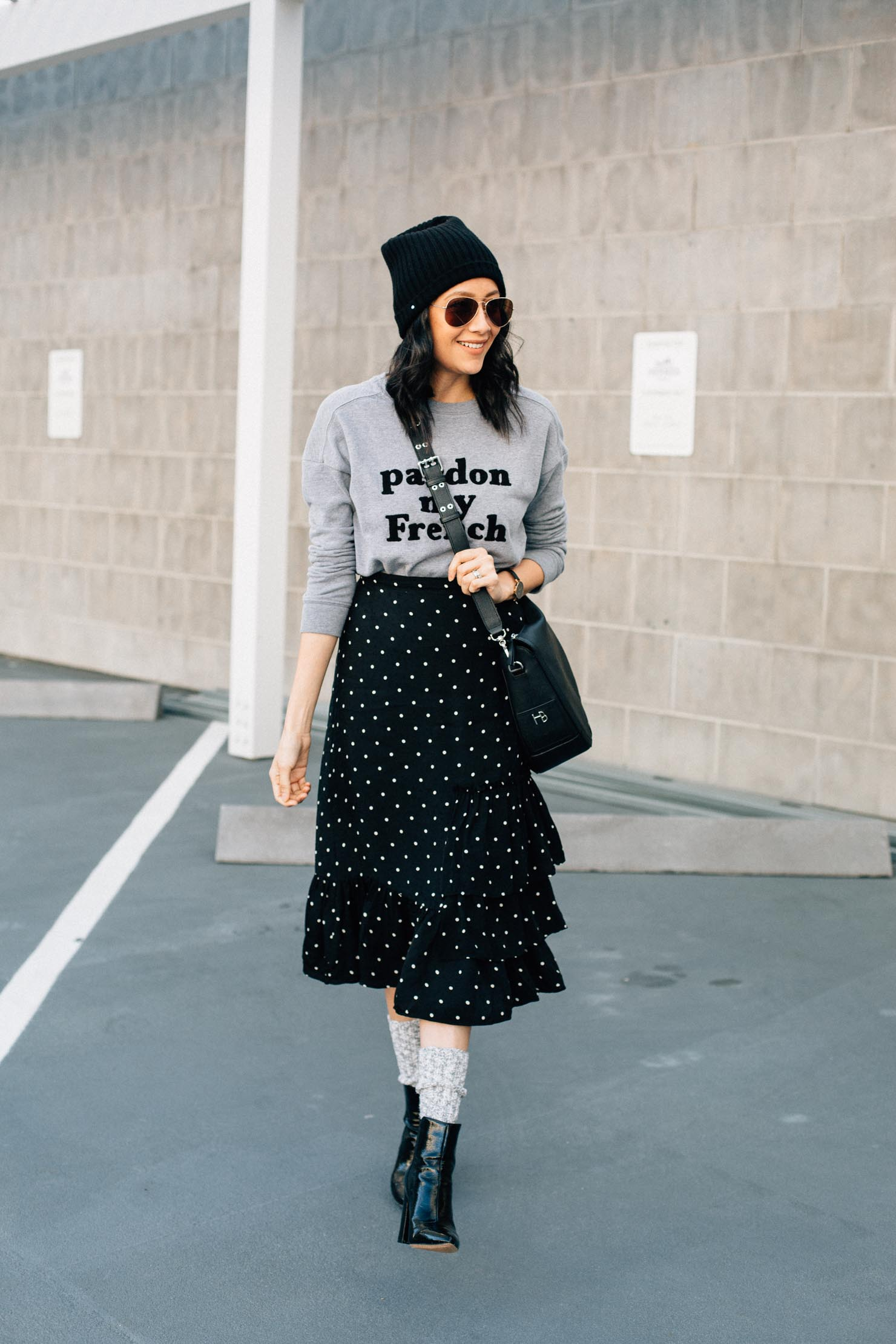 Fashion blogger Lilly Beltran styles a midi length polka dot skirt with a grey sweatshirt, grey beanie and boots & socks for an effortless chic winter outfit