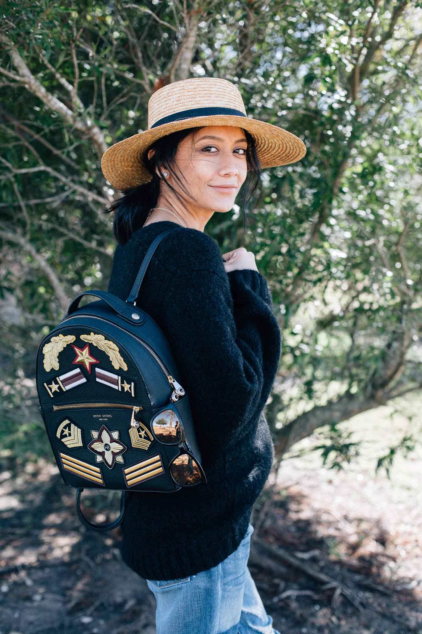 Houston Based Fashion Blogger Lilly Beltran wears a straw hat with an oversized sweater and a Henri Bendel backpack