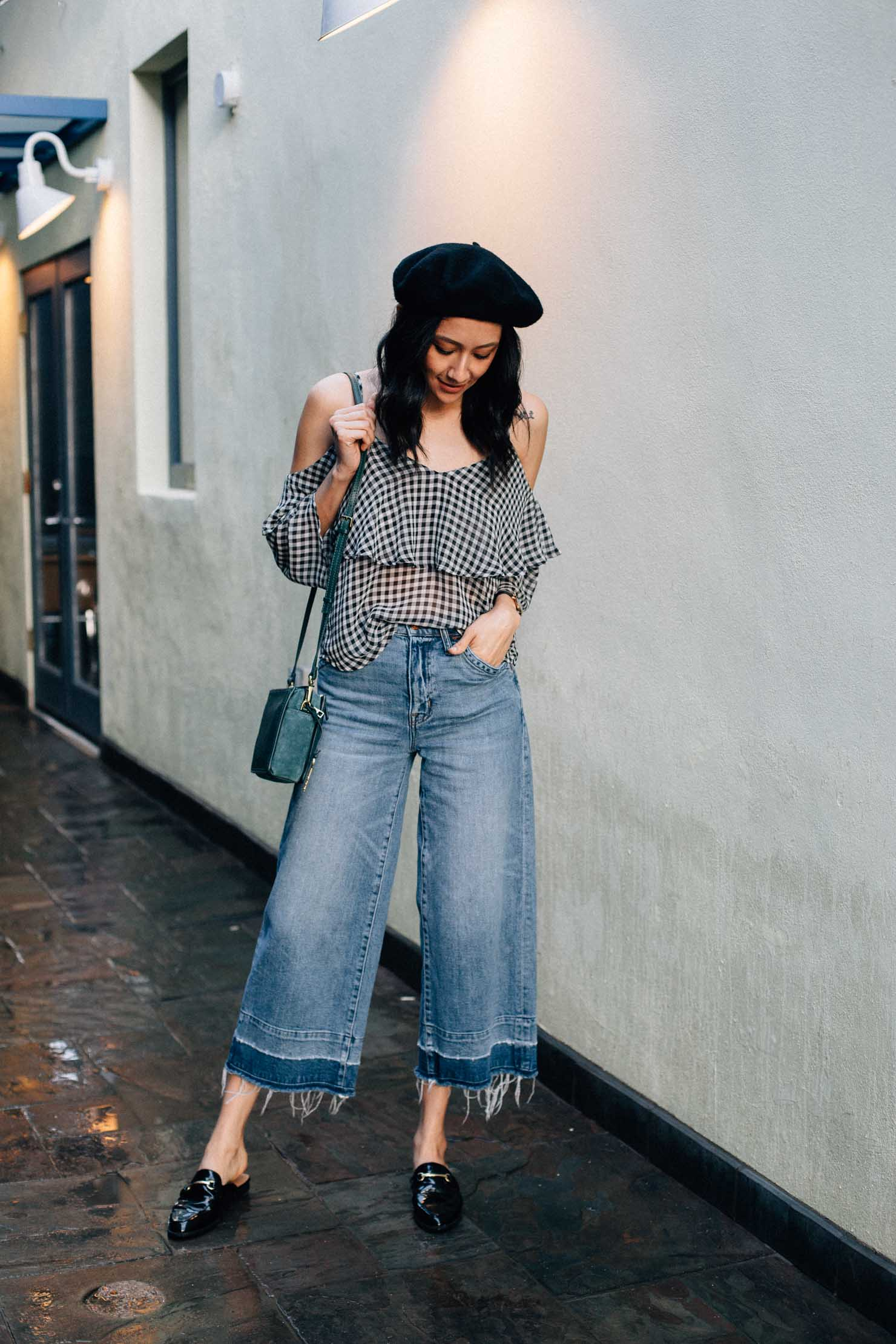 Fashion blogger Lilly Beltran wears wide leg denim with a gingham top, loafer mules and a black beret.