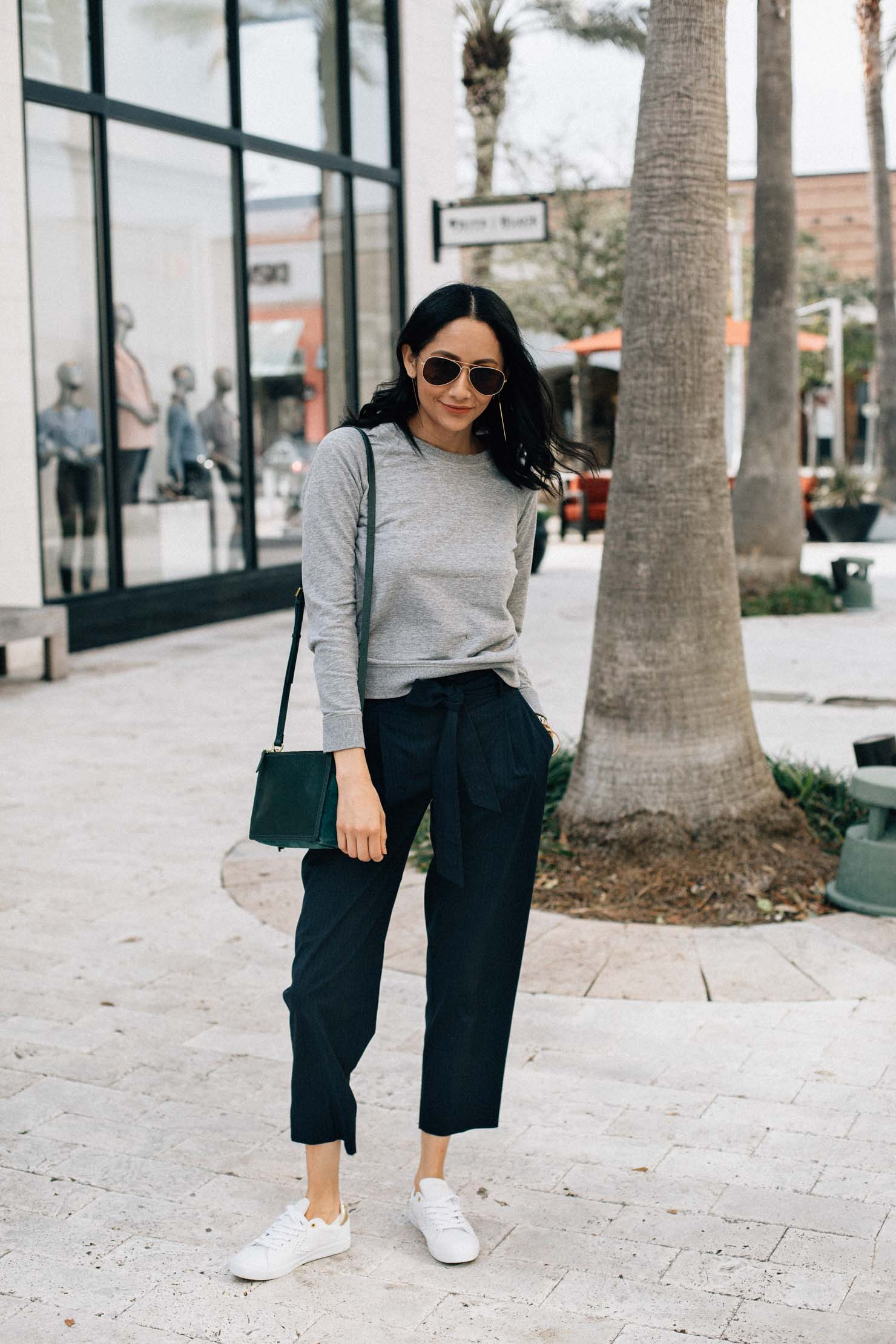 Lilly Beltran of Daily Craving blog in a casual chic outfit wearing white sneakers and slacks