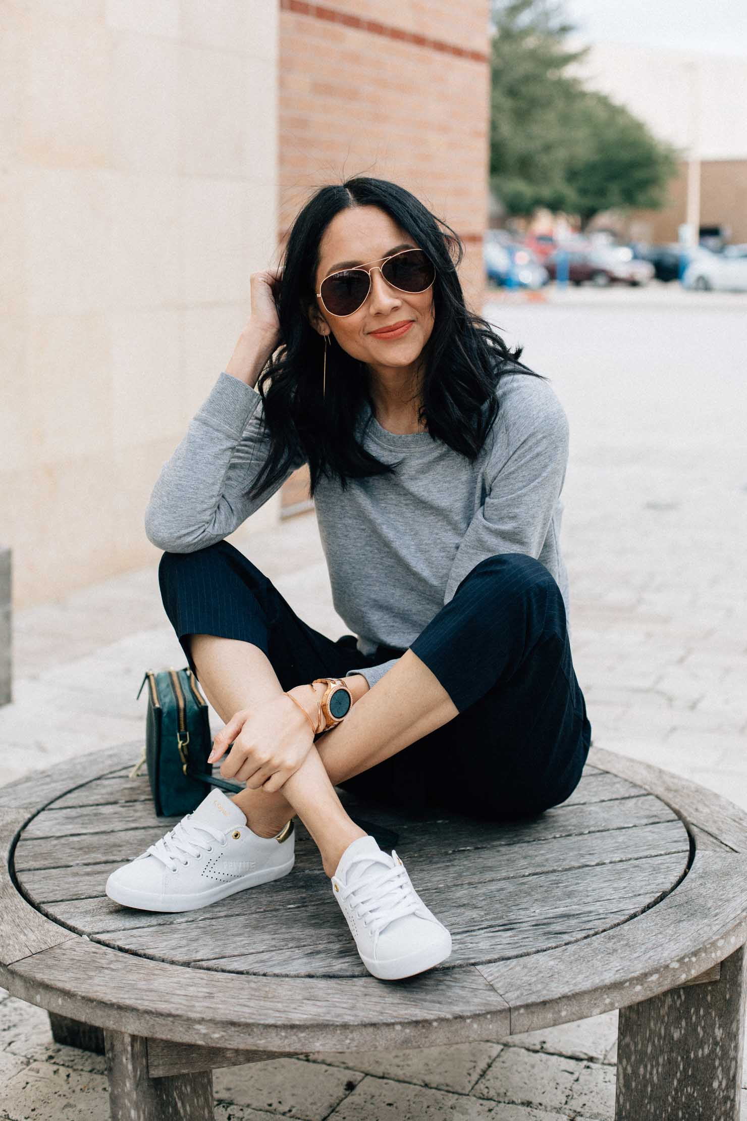 fashion blogger Lilly Beltran wears navy slacks with a grey sweatshirt and white sneakers for an effortless look