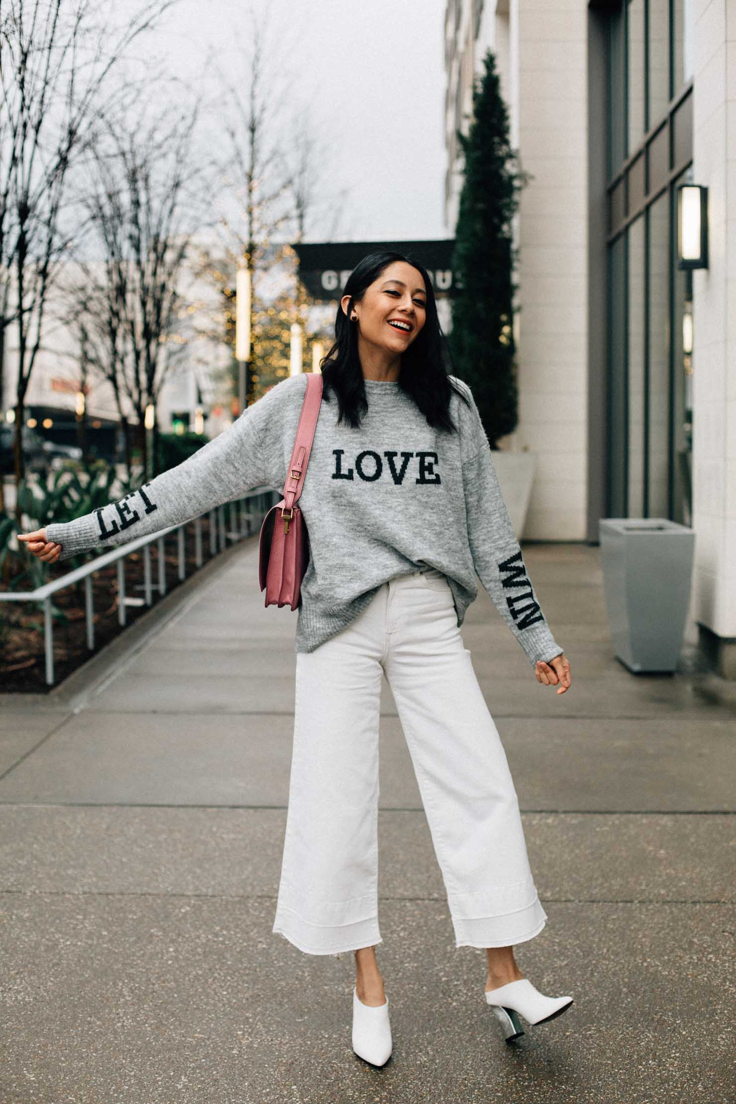 Fashion blogger Lilly Beltran in white wide leg denim, white mules and pink Fossil Bag