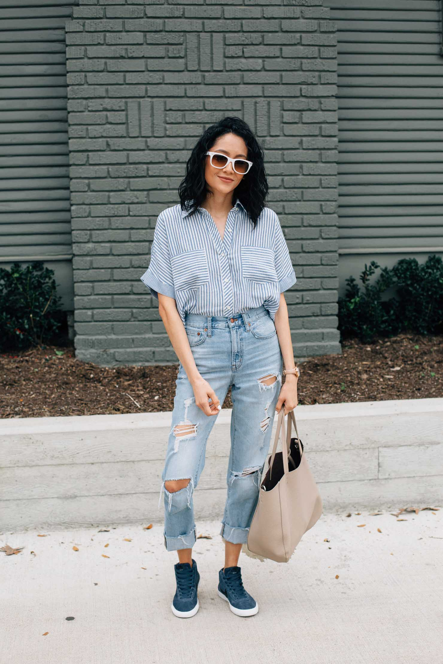 Houston based style blogger Lilly Beltran pairs high waisted denim with Nike hightop sneakers for a casual look