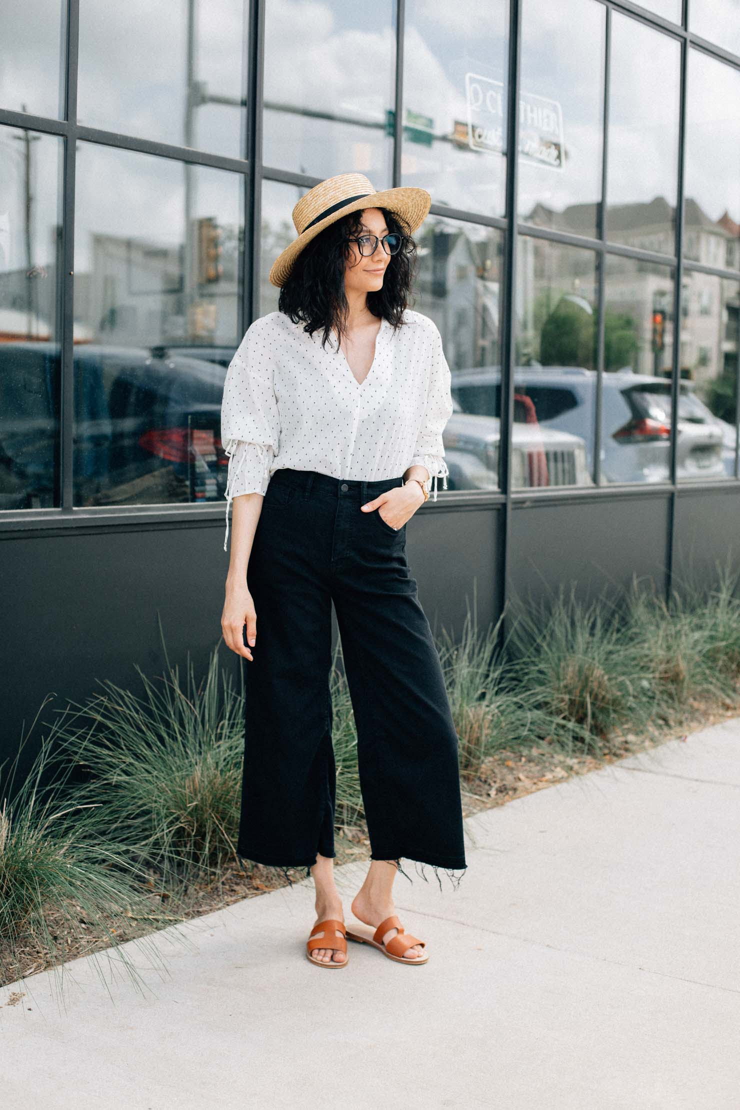 Lilly Beltran in a spring look wearing wide leg denim with a bell sleeve shirt and a straw hat
