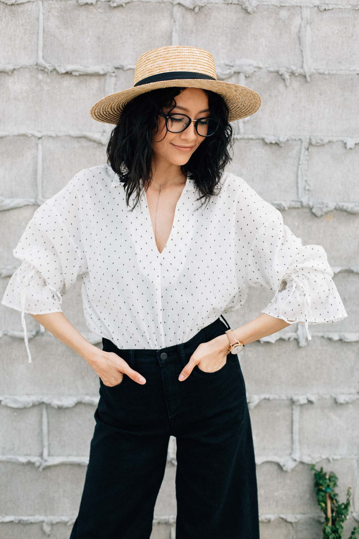 Lilly Beltran of Daily Craving blog styles a bell sleeve shirt with a straw hat and wide leg denim for an effortless spring look