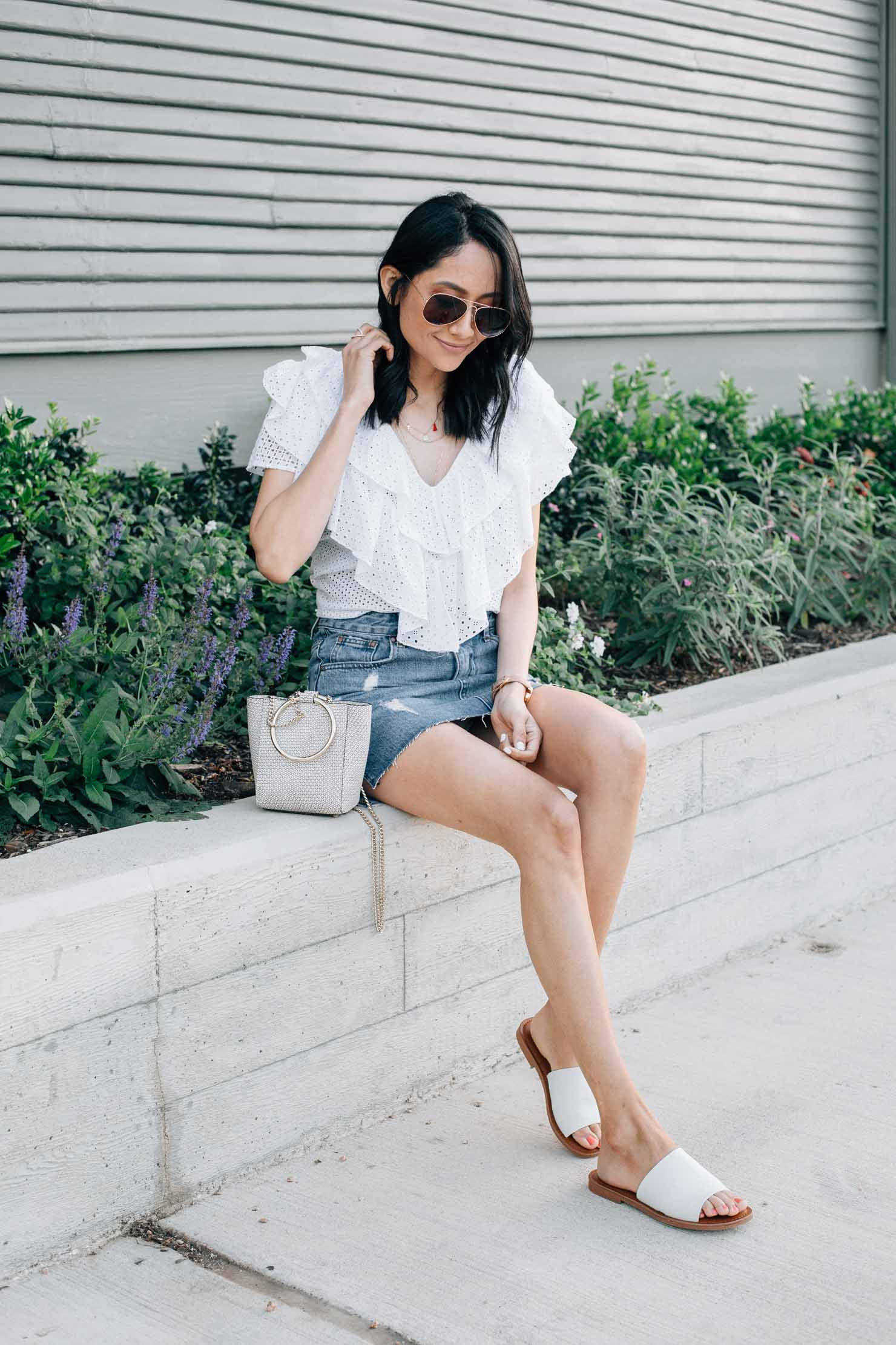 fashion blogger Lilly Beltran wearing a Zara white eyelet top with a denim mini skirt and white slides for a feminine summer look