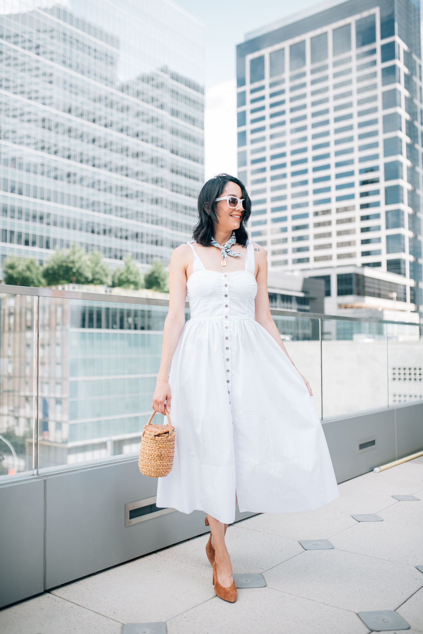 Fashion blogger Lilly Beltran wearing white for summer in a Chicwish midi length dress, brown pumps and basket bag for a fresh summer look.