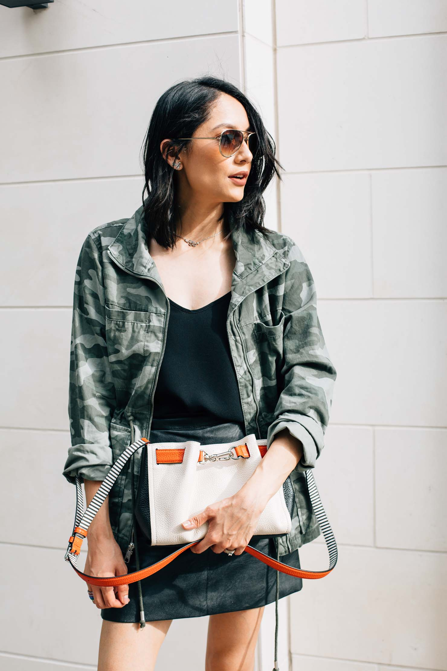 A camo jacket worn with a leather mini skirt by blogger Lilly Beltran