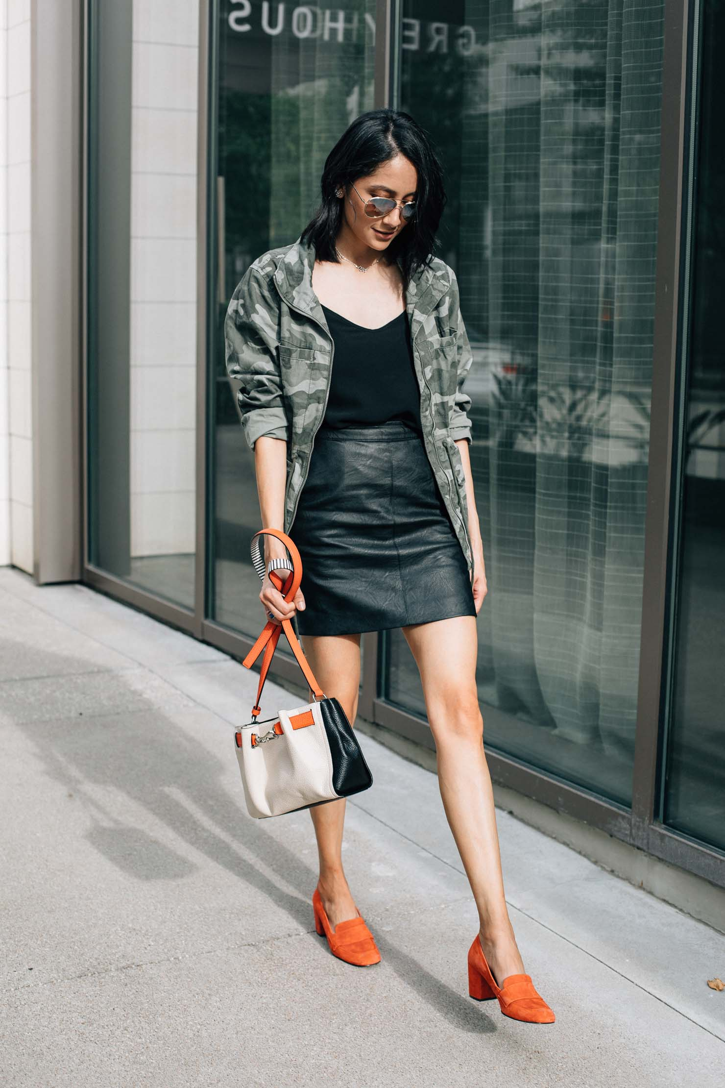 Style blogger Lilly Beltran wearing a black leather skirt with an Old Navy camo jacket and block heel loafers