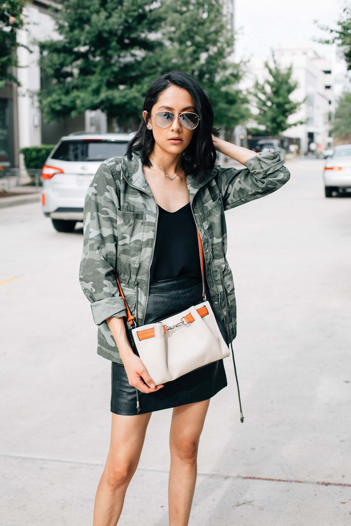 Camo jacket styled with leather mini skirt and Henri Bendel crossbody bag by Lilly Beltran from Daily Craving blog.