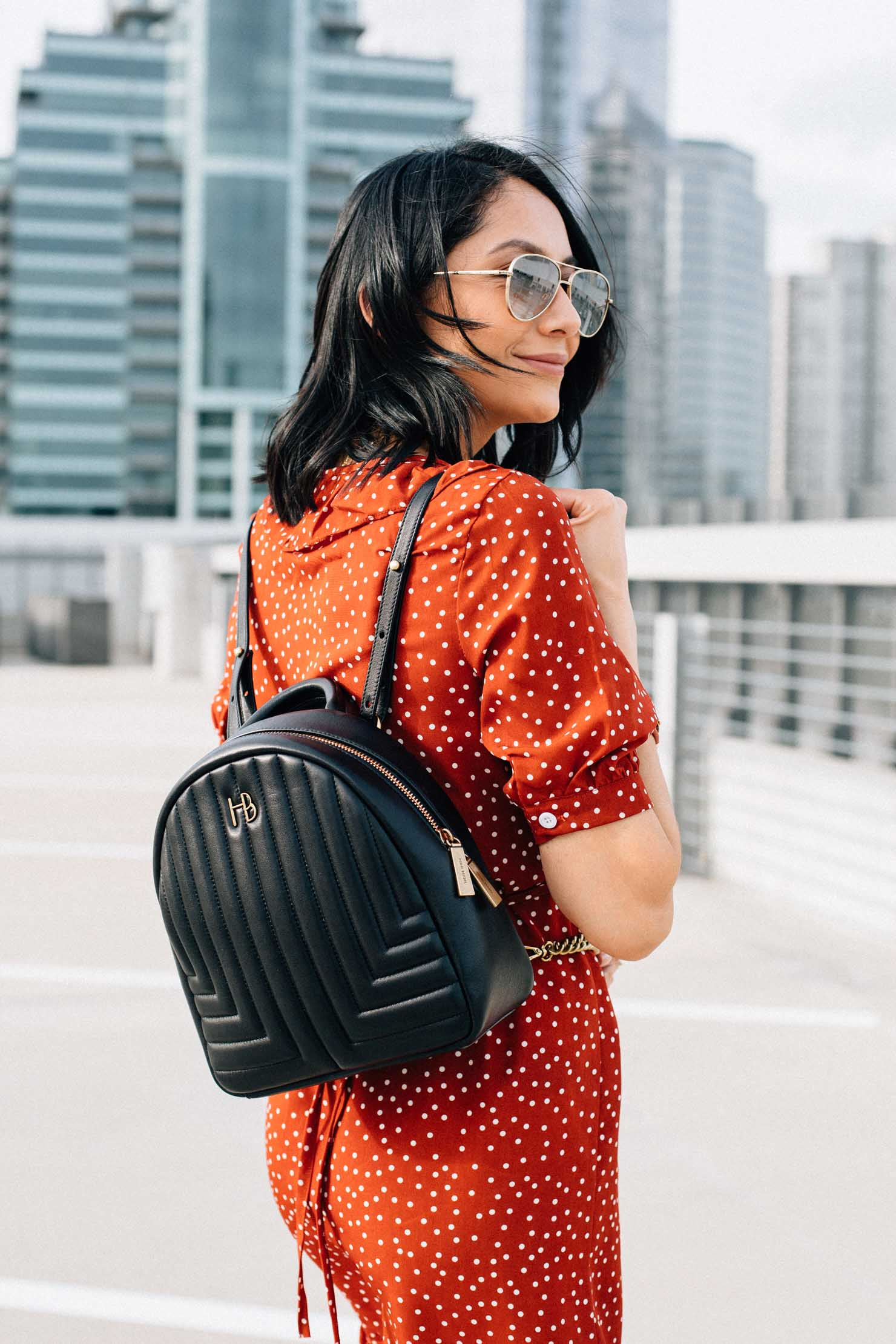 Style blogger Lilly Beltran of Daily Craving blog wearing a red polka dot dress from chic wish and a Henri Bendel Backpack purse