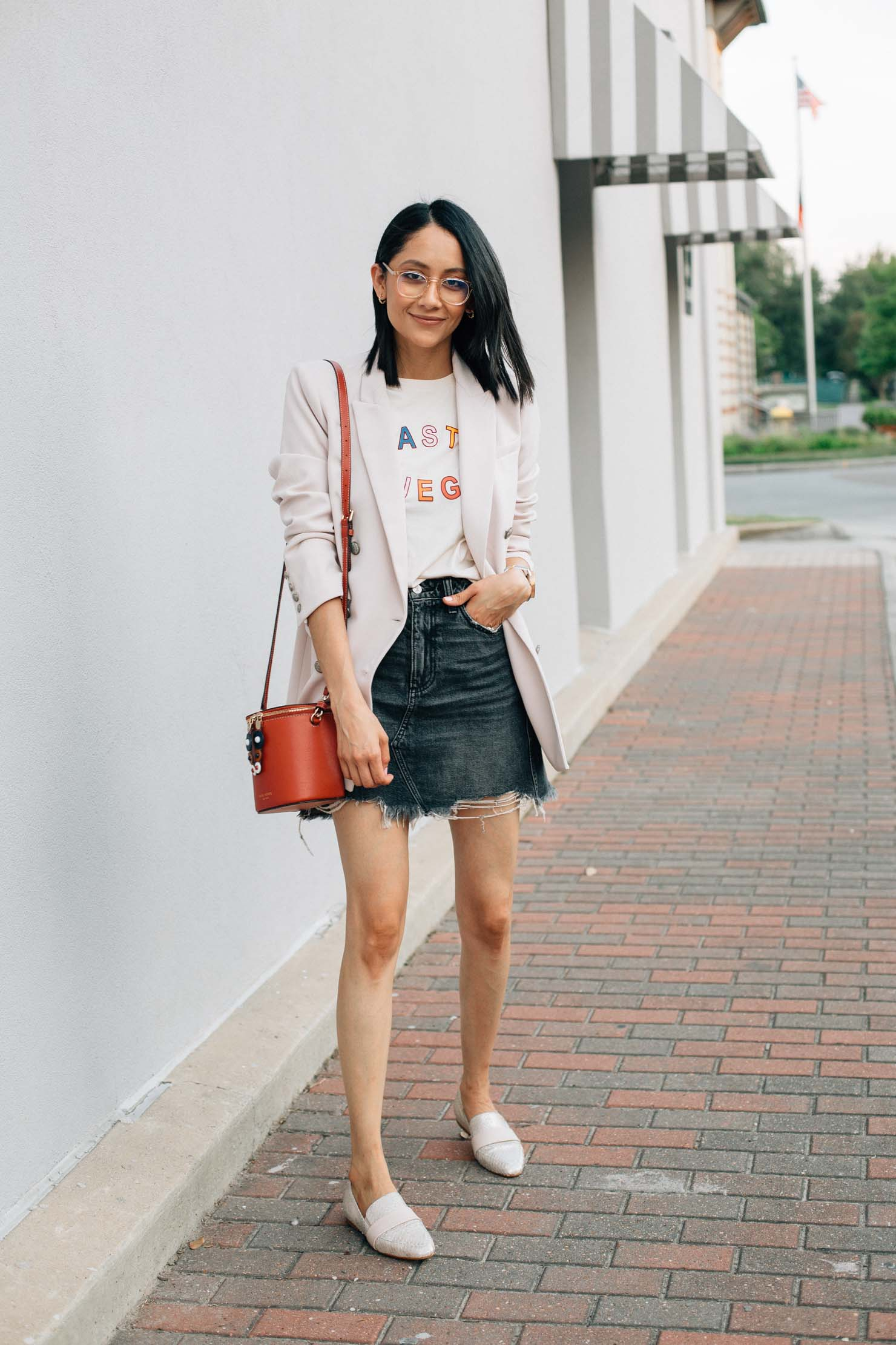 A fall outfit with a denim skirt, blazer and graphic tee.