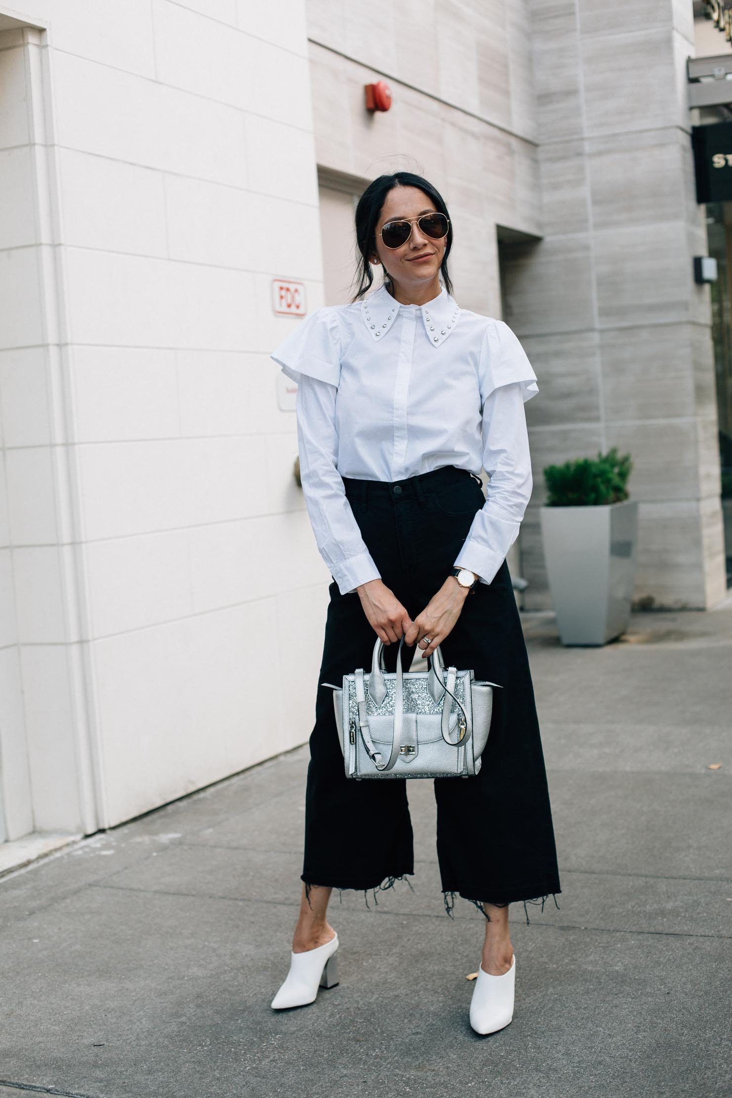 Lilly Beltran in a holiday ready look with black pants, white mules and studded collar top.