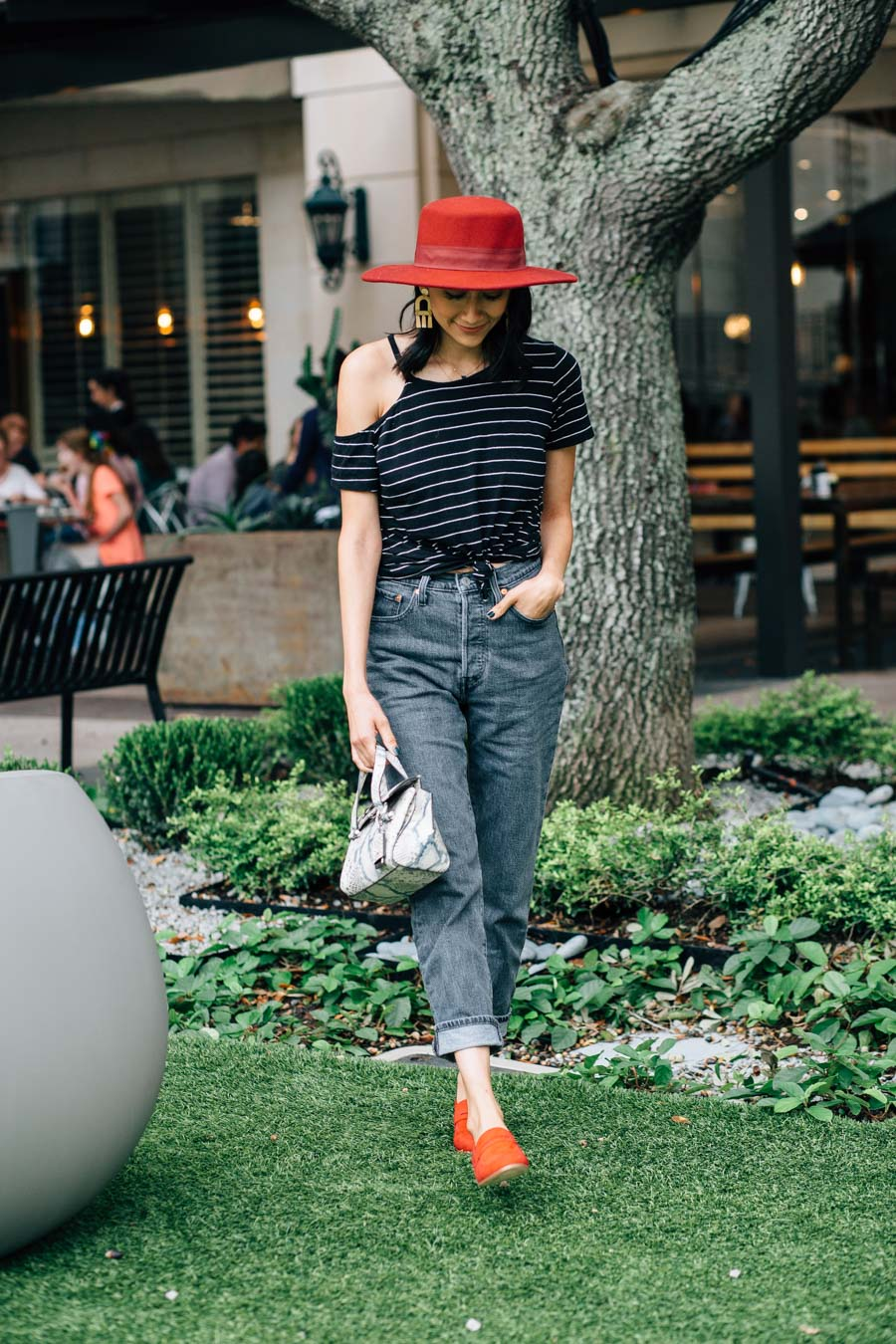 Lilly Beltran wearing Levi's 501 mom jeans with a black striped t-shirt and red loafers