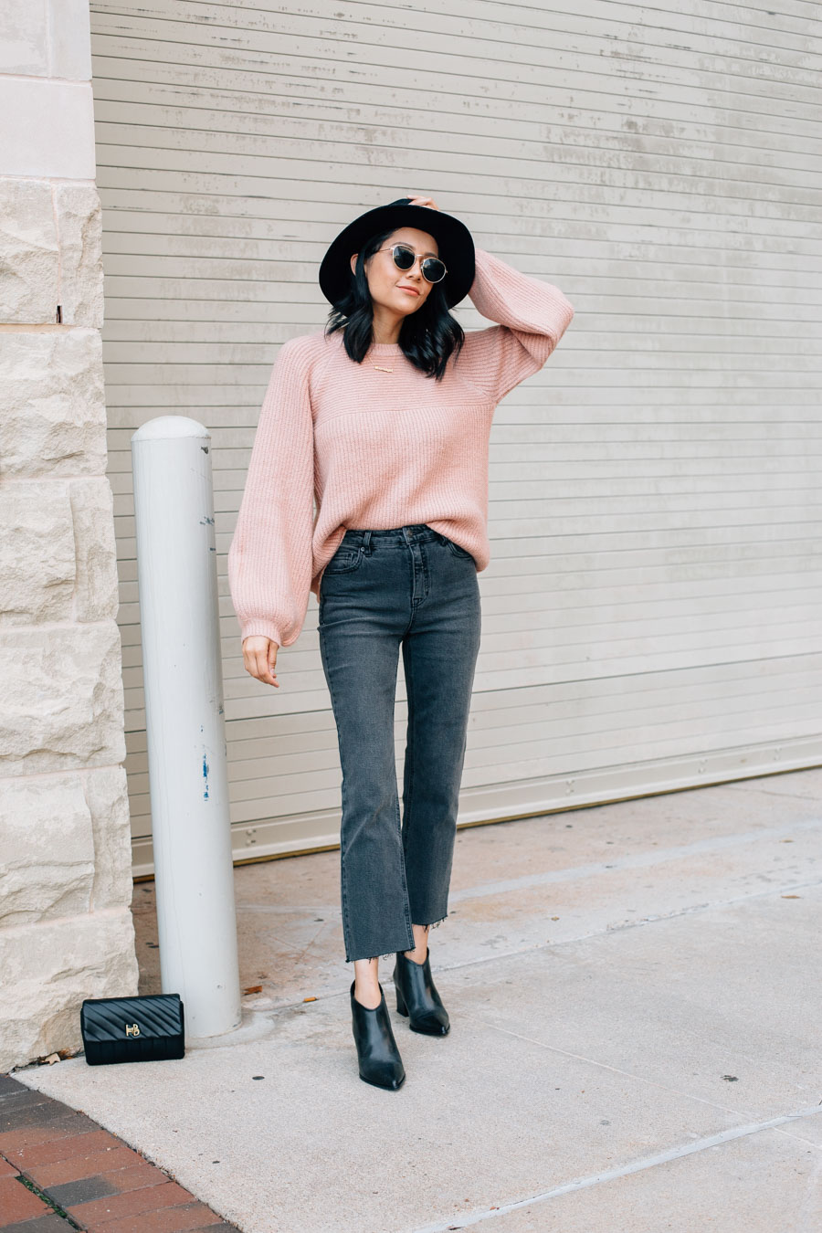 Lilly Beltran wearing a pink sweater from Francesca's and black cropped flare leg jeans.