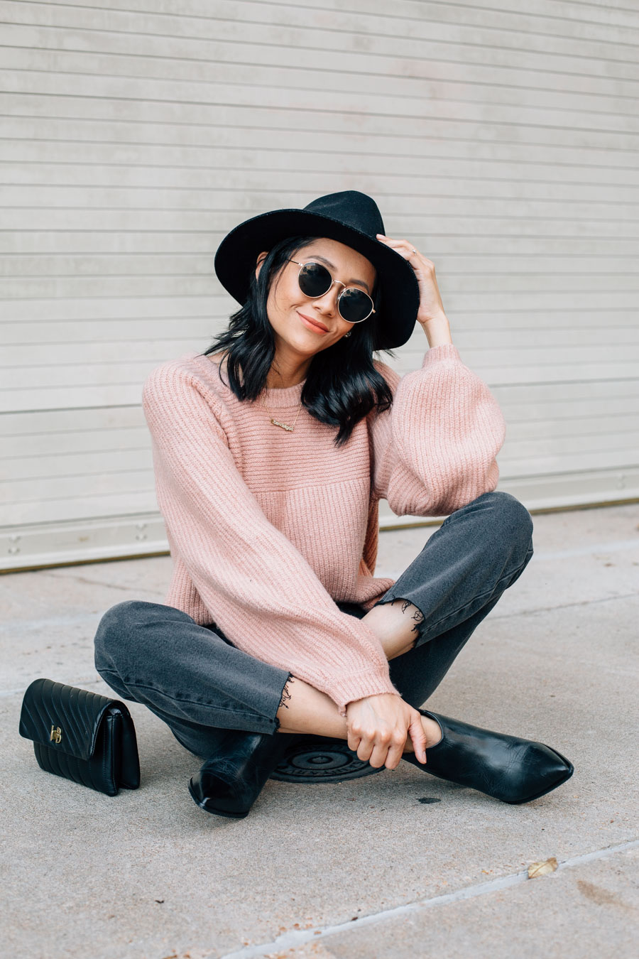 Blogger Lilly Beltran wearing a fall look with black denim and a pink ballon sleeve sweater.