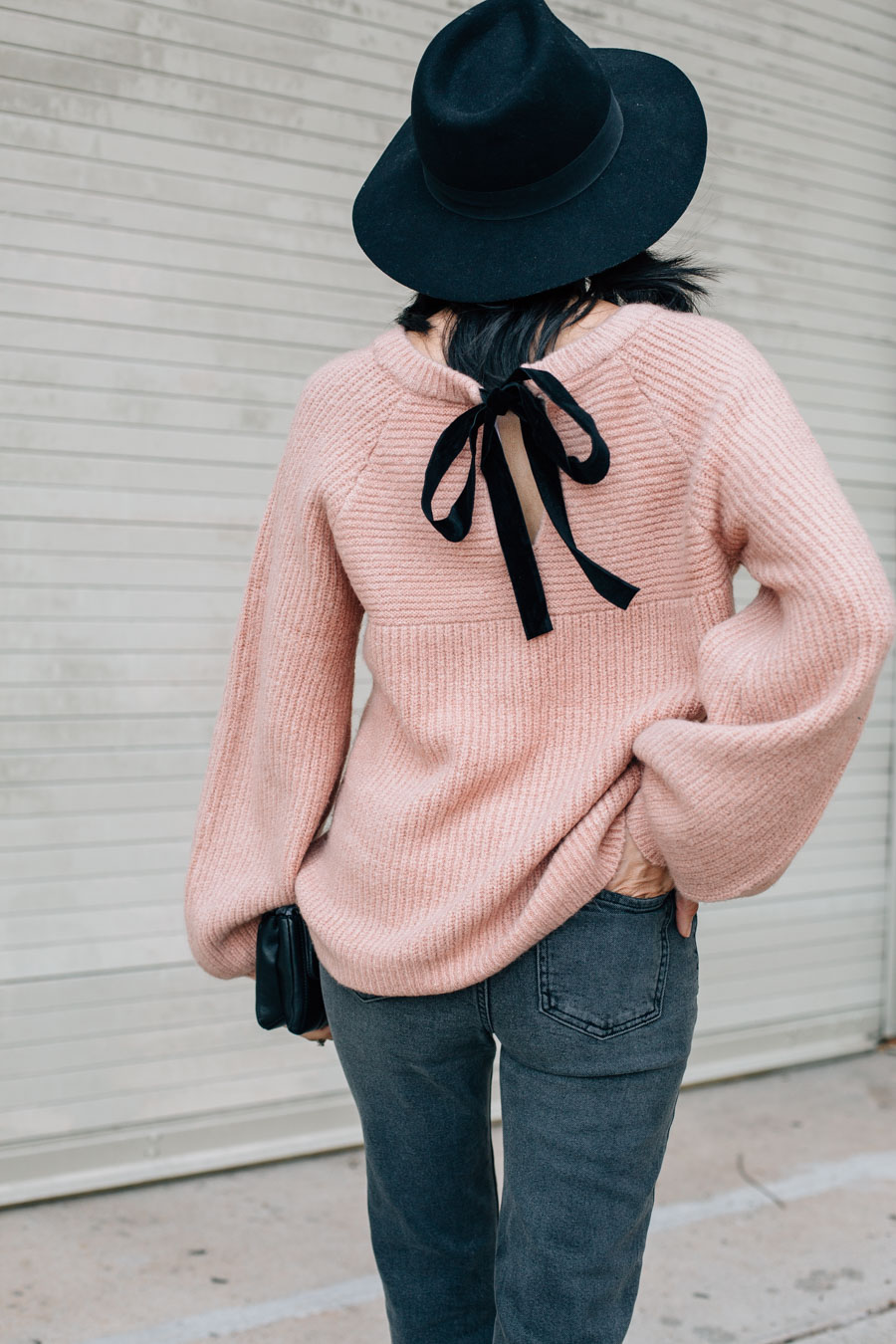 Style blogger Lilly Beltran wearing a chunky pink sweater with balloon sleeves and a black velvet bow on the back