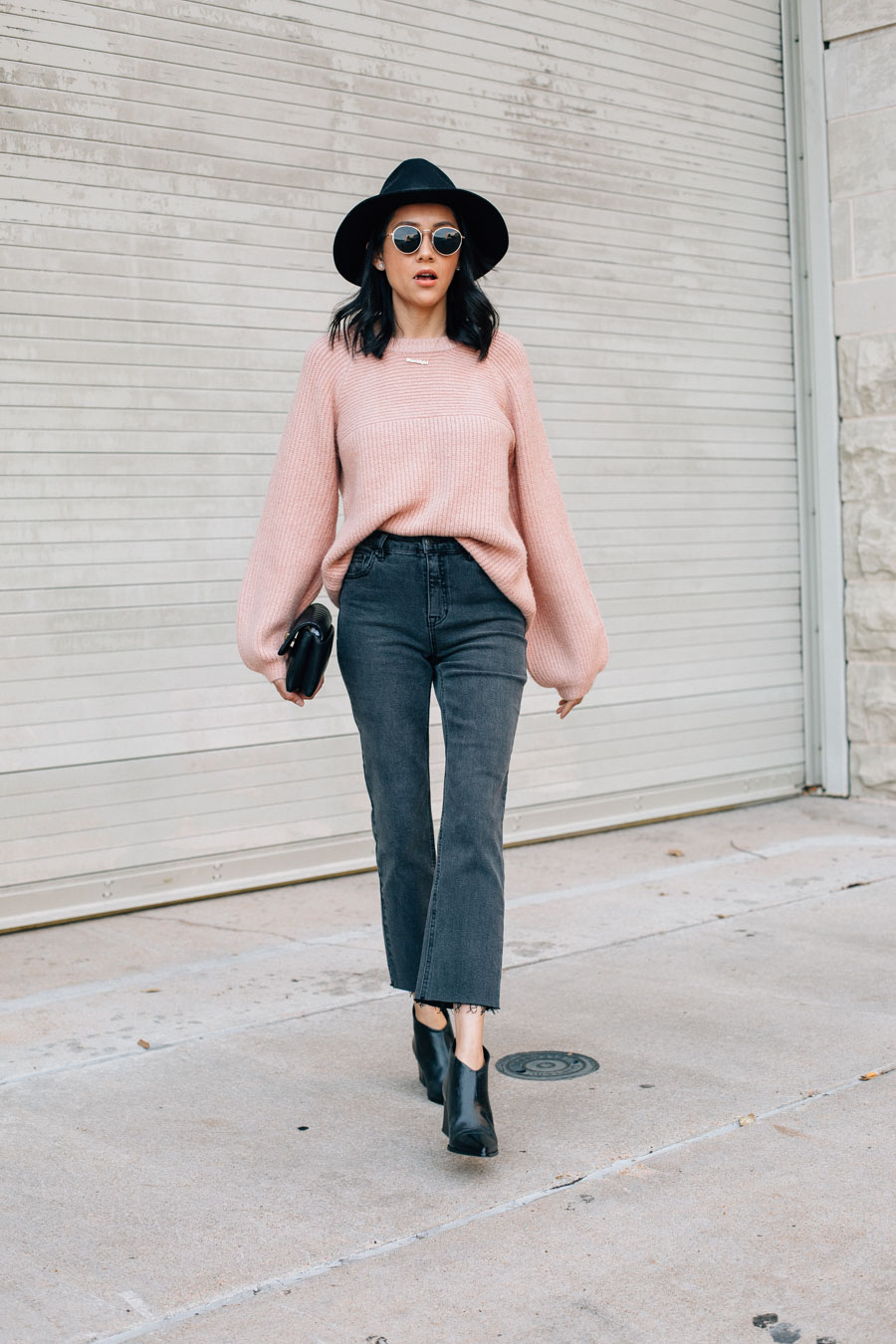 Style blogger Lilly Beltran in a chic fall outfit with black jeans, pink sweater, fedora hat and black leather booties.