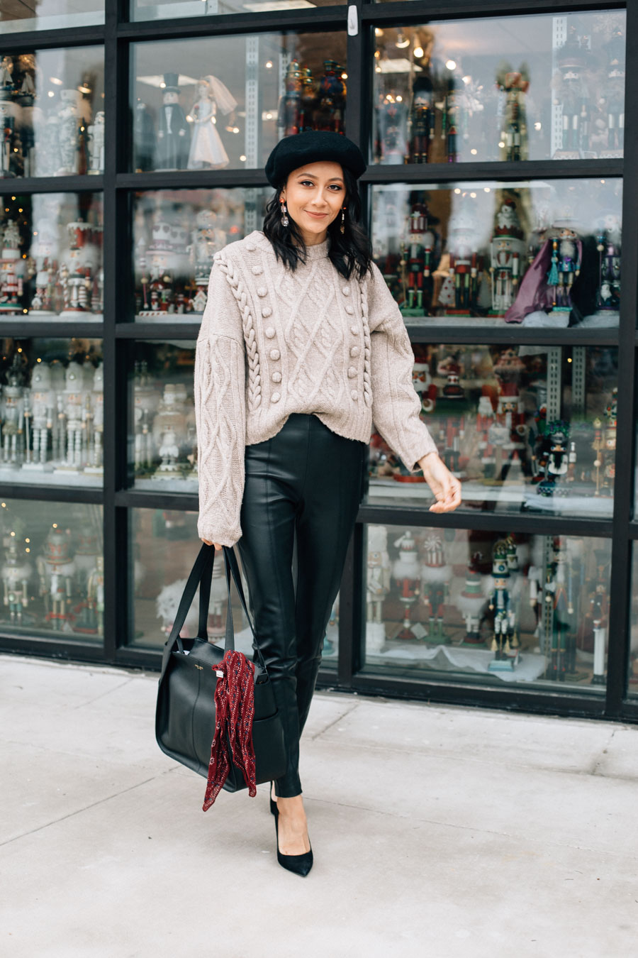 Fashion blogger Lilly Beltran in a casual holiday party look with leather leggings and cable knit sweater
